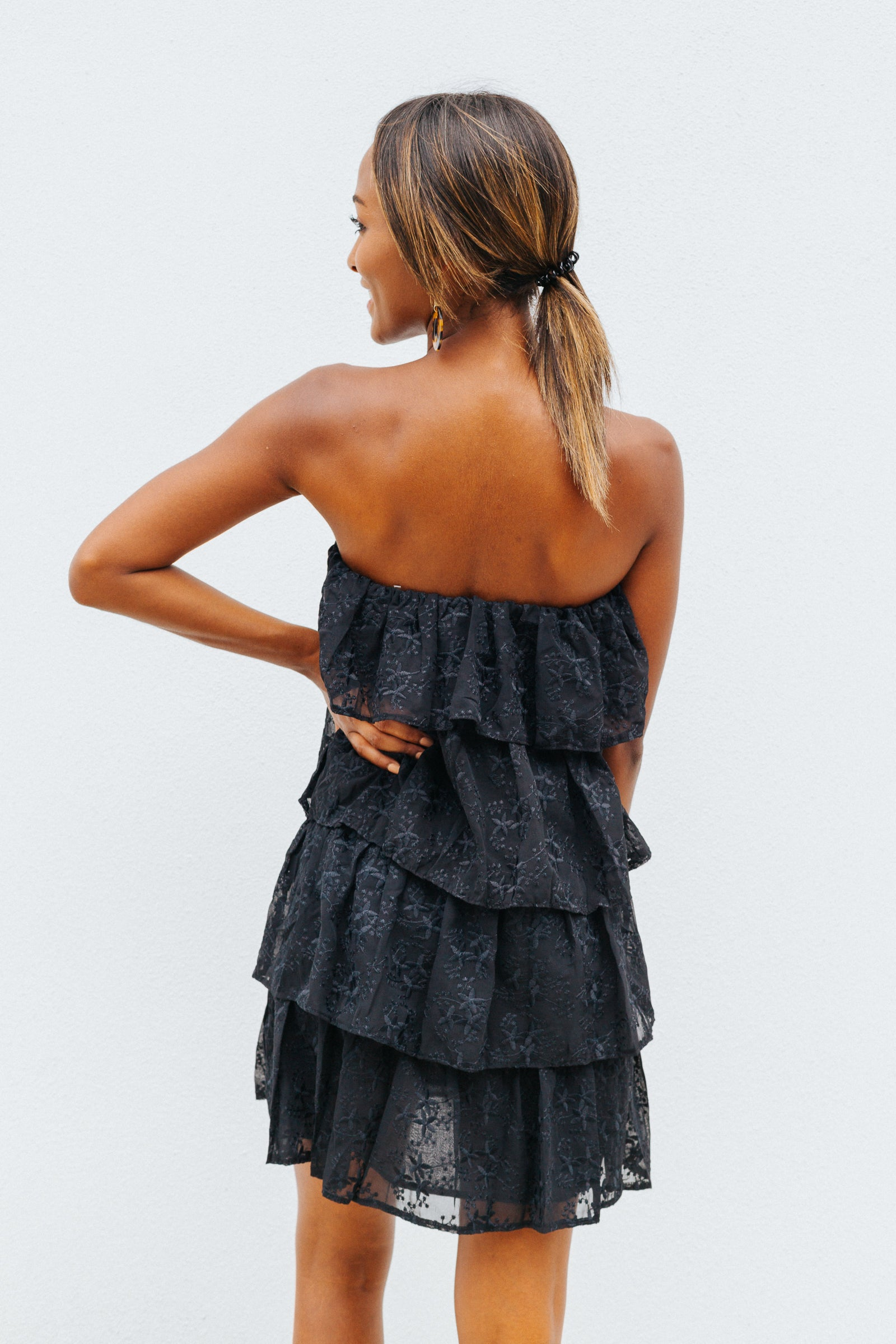 Black floral and leaf prints are embroidered on this gorgeous black mini dress. It has a straight neckline and goes down into a ruffle layered and oversized dress silhouette.