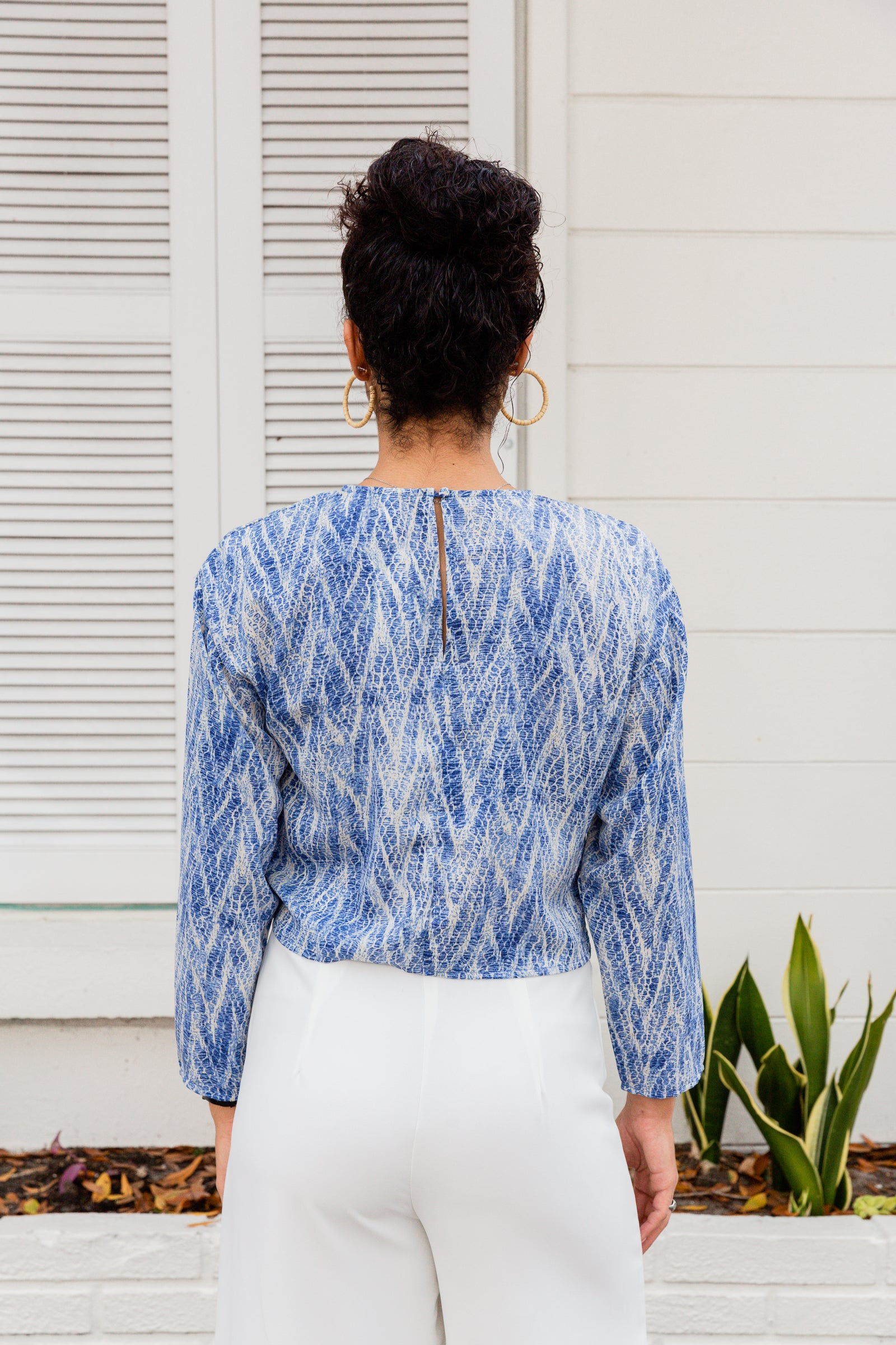 Blue and white prints go across the fabric of this lightweight blouse. Long sleeves attach to a high u-neckline on a relaxed fit bodice silhouette before meeting a twisted front hem.