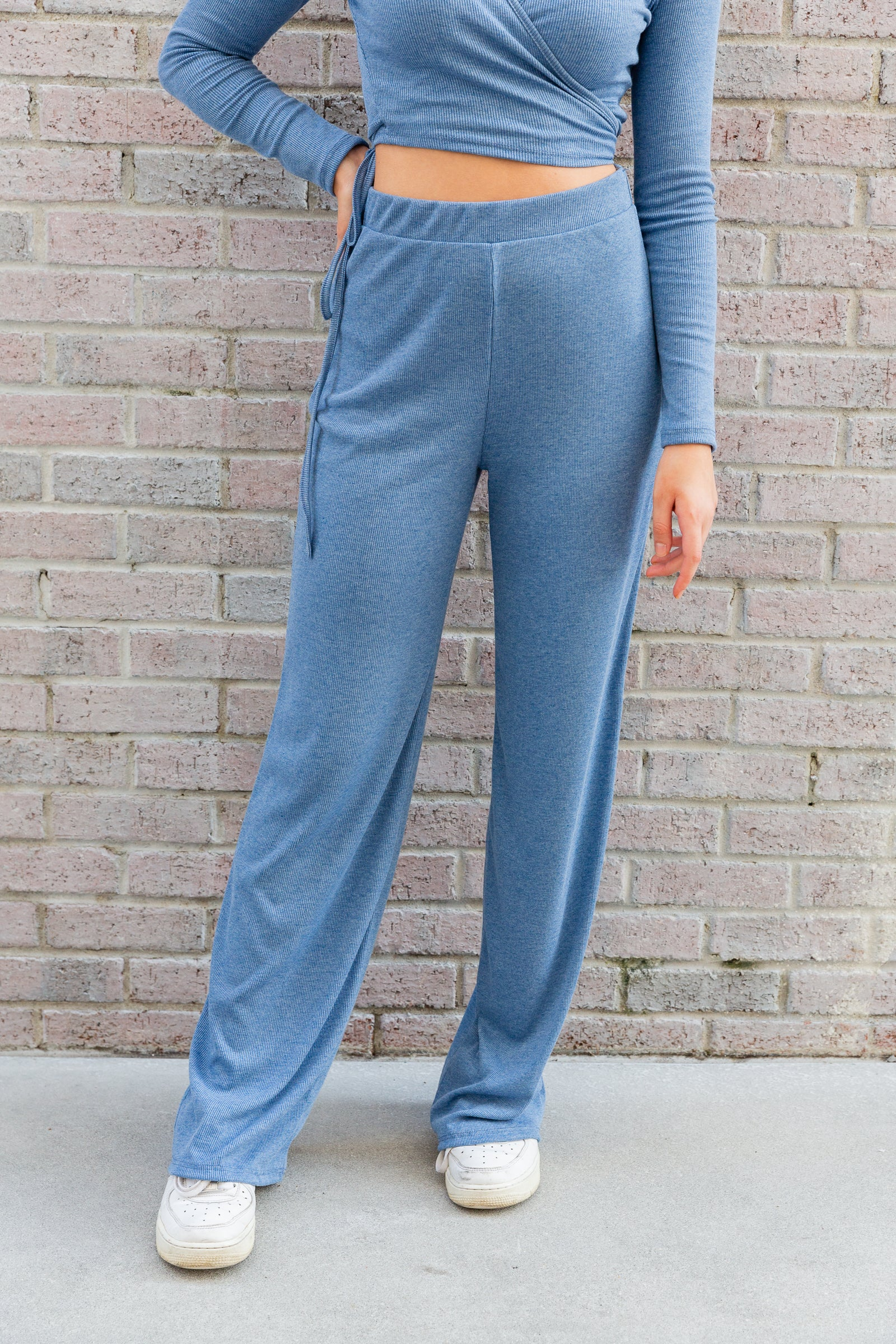 These lounge pants are ribbed with an elastic waistband that is high-fitted and hip-hugging then flows down into gently flared pant legs.