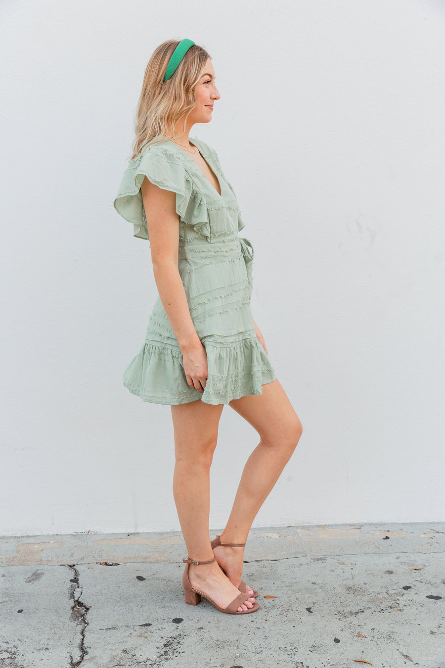 Small textured frays cover the fabric of this feminine dress. Short flutter sleeves attach to a surplice neckline and go into a ruffle-trimmed skirt panel with a side-tied waistline.