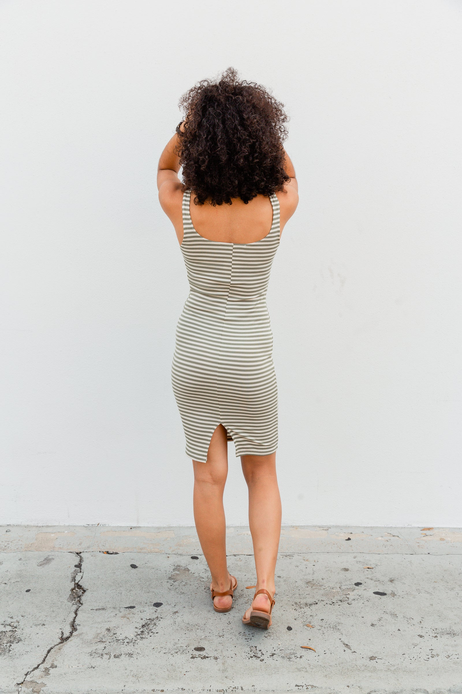 Olive and cream stripes go across the fabric of this ribbed dress. Medium straps attach to a square neckline on a fitted and hip-hugging dress.