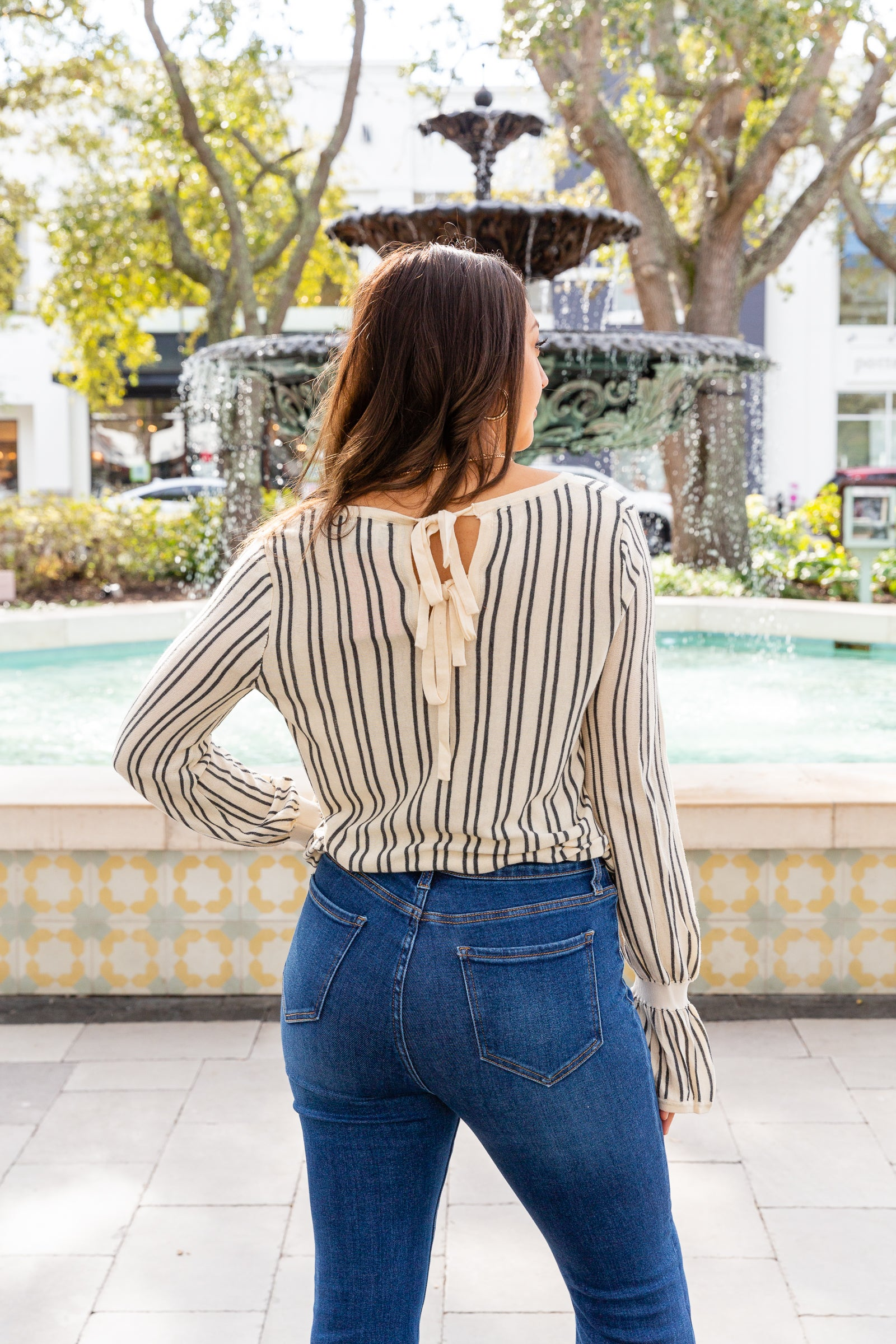 Stripes go down the lightweight fabric of this patterned sweater. Long elastic ruffle cuffed sleeves attach to a crew neckline on a relaxed-fit and loose bodice silhouette.