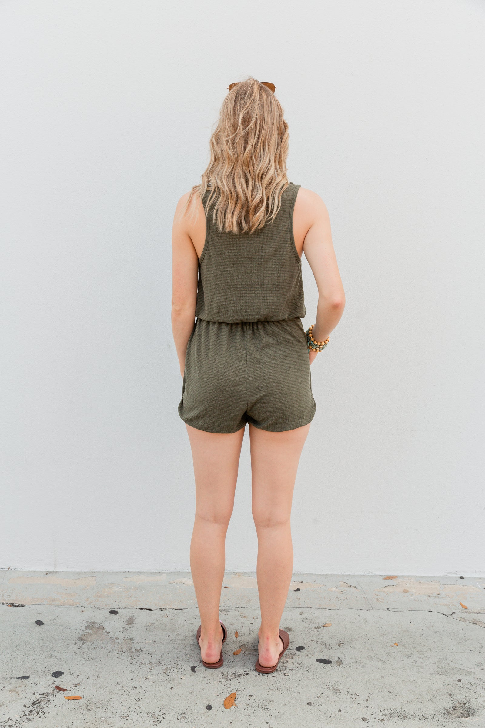 This comfy romper has medium straps that attach to a v-neckline with a button-down clasp center leading to an elastic waistband before meeting side pockets and relaxed fit shorts.