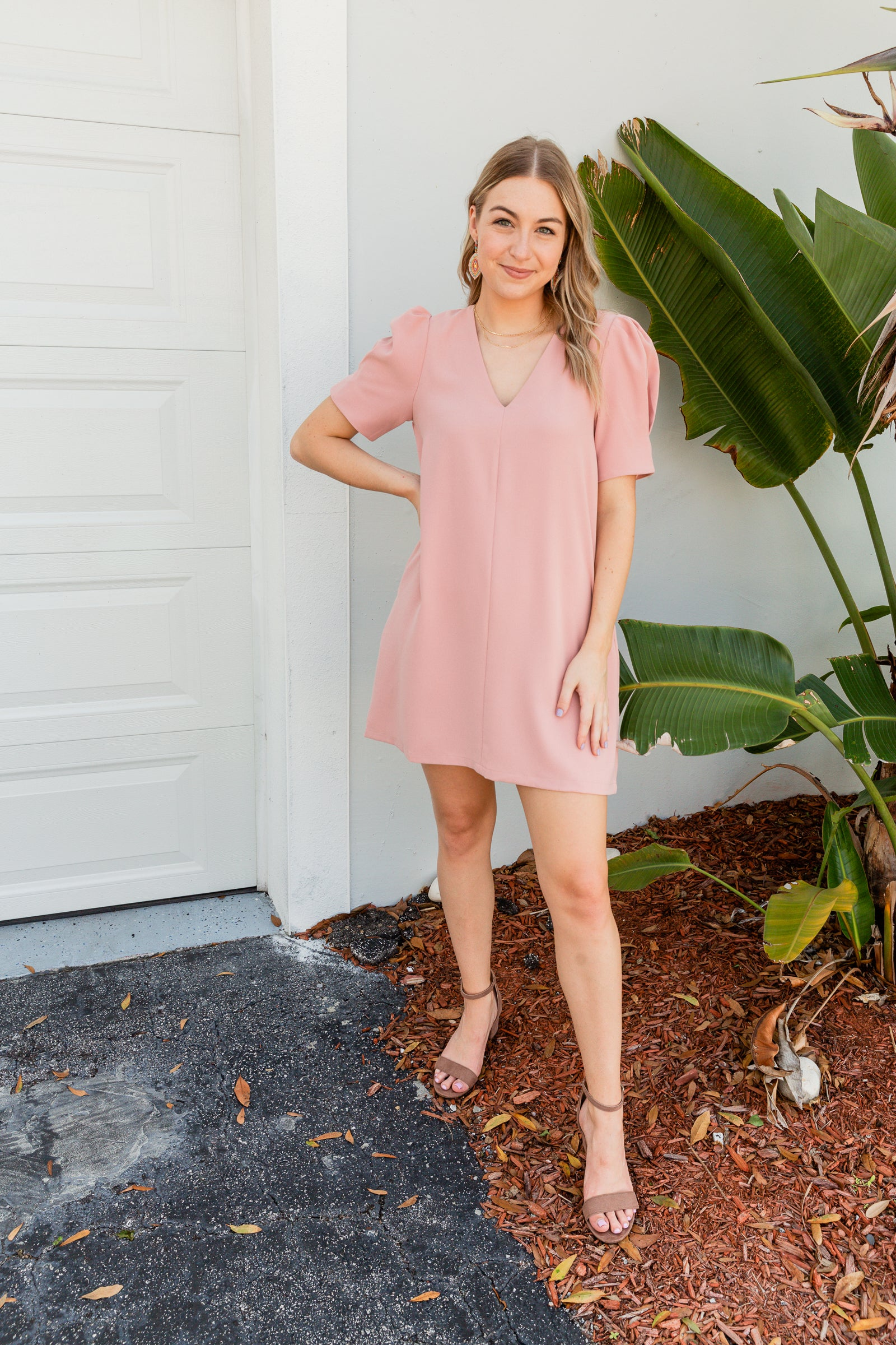 This pink dress has short puff sleeves that attach to a deep v-neckline on a loose paneled shift silhouette with side pockets.