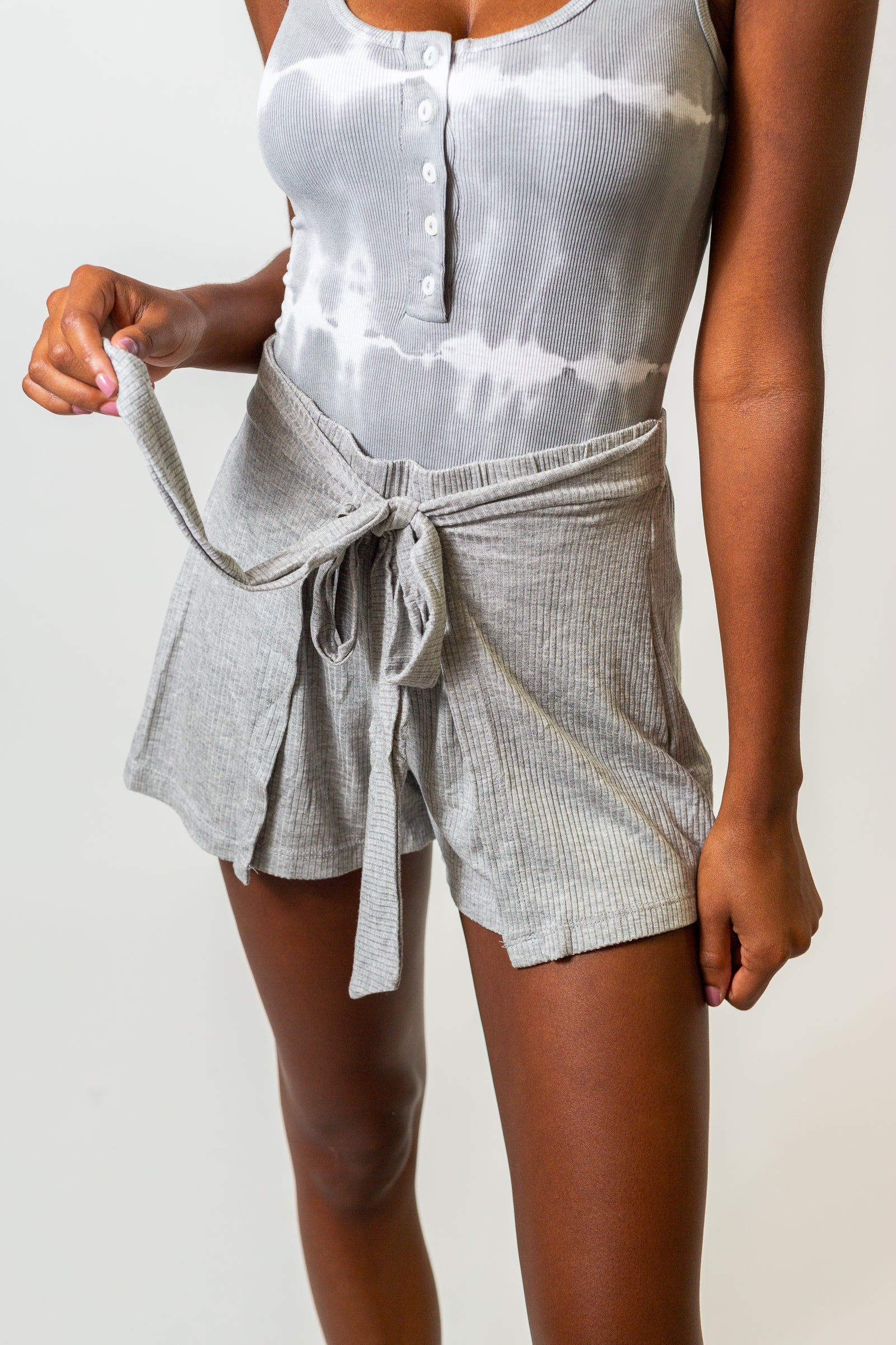 These comfy ribbed shorts have an elastic waistband with fabric panels coming from each side to tie at the front of these loose shorts.