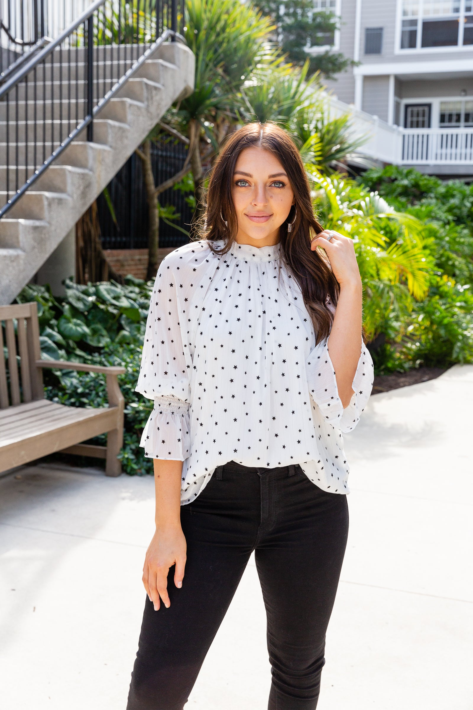 Small black stars speckle the lightweight fabric of this blouse. Long elastic ruffle cuffed sleeves attach to a mock neckline on a loose and relaxed-fit bodice silhouette.