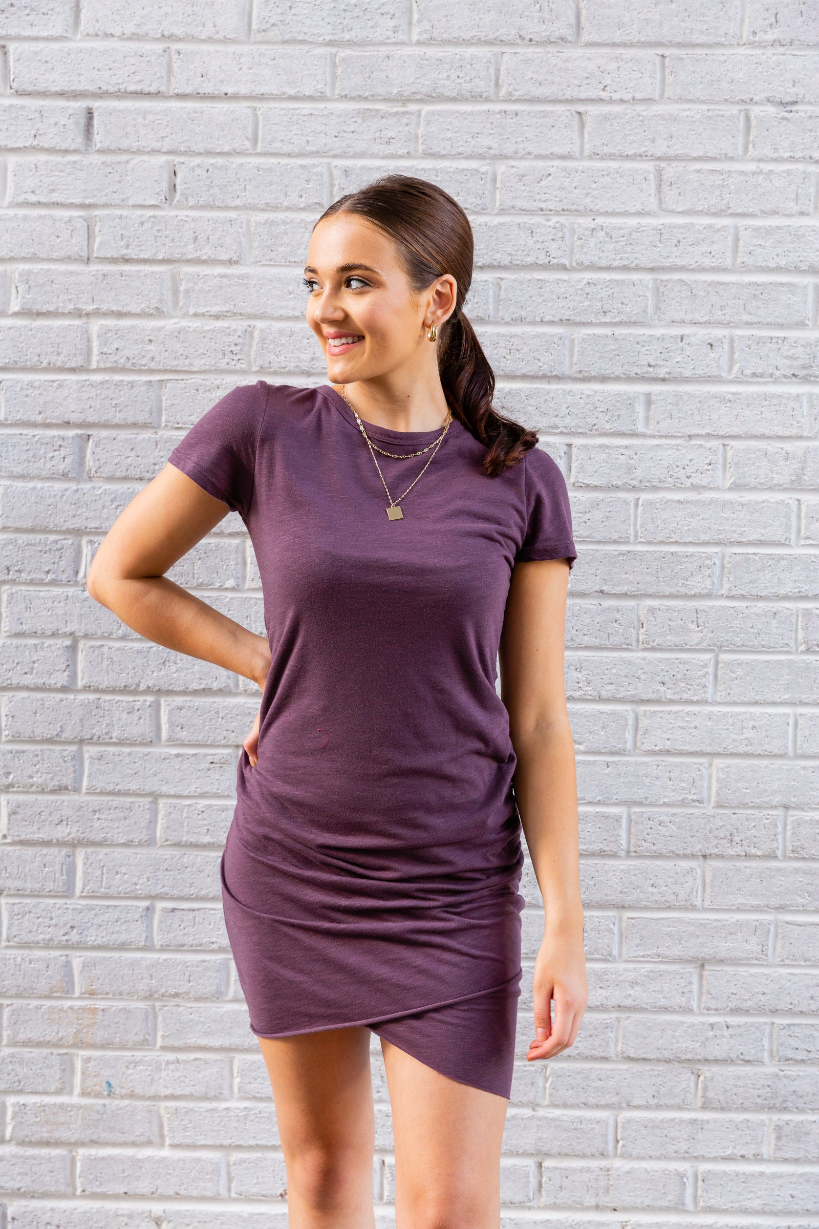 Short sleeves attach to a u-neckline and lead to a loose bodice and skirt silhouette with ruching details down one side of the dress for an asymmetrical hem at the bottom.