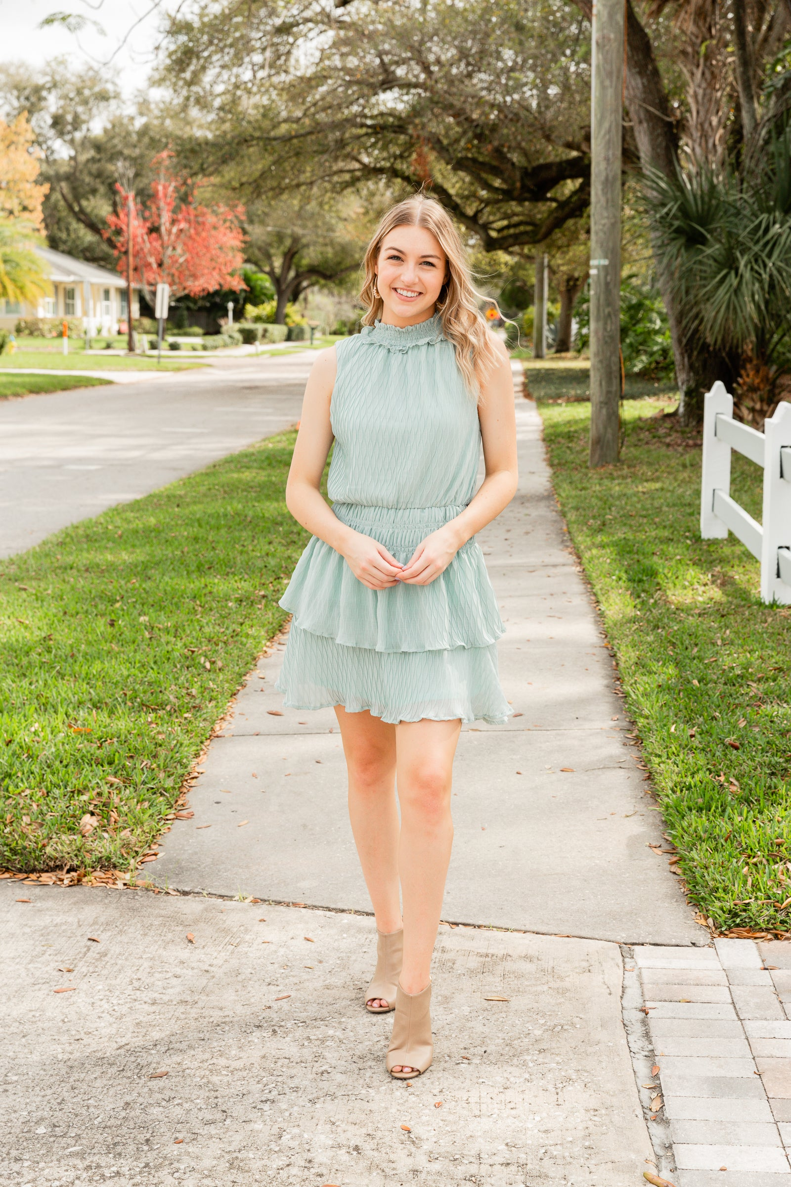 This lightweight and textured dress is sleeveless with a smocked mock neckline that attaches to a relaxed bodice silhouette and meets a smocked waistband before going into a layered ruffle skirt.