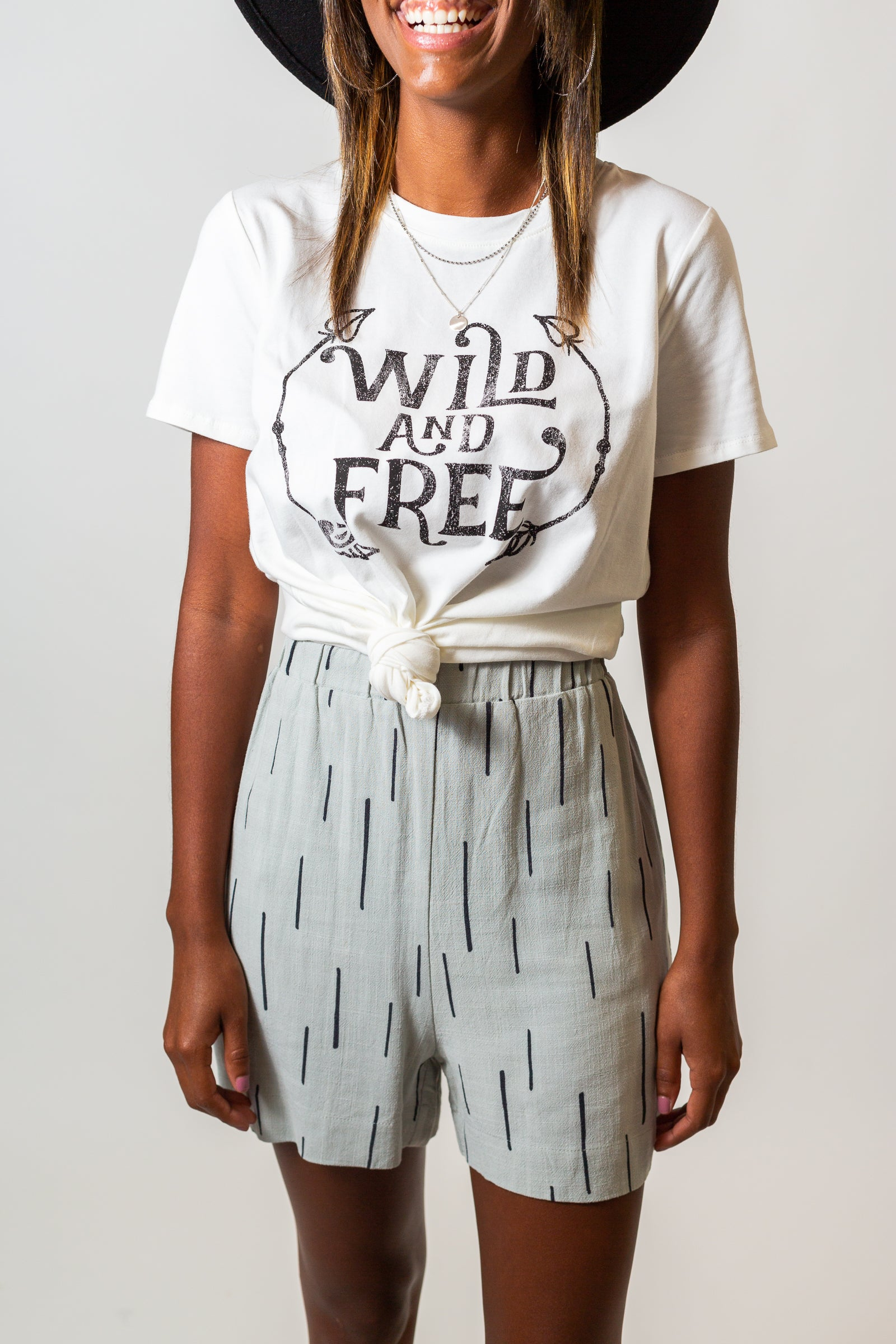 "Short sleeves attach to a banded u-neckline on a comfortable and relaxed fit bodice silhouette. The words ""Wild and Free"" are faded with arrows curving upwards around the vintage-vibe text."