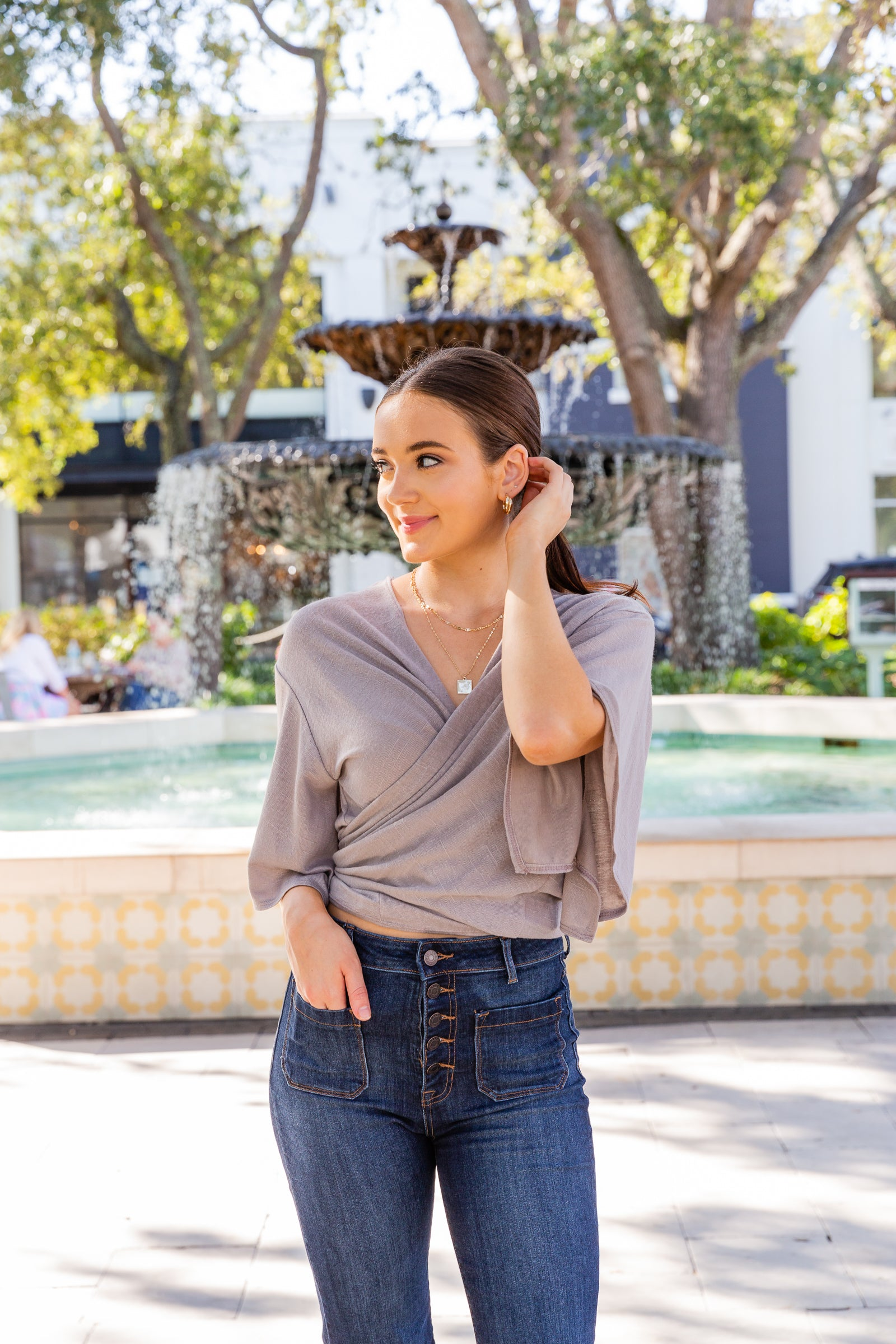 This lightweight knit top has mid-length loose sleeves that attach to an oversized and open front bodice with an asymmetrical hem and flowy fit bodice.
