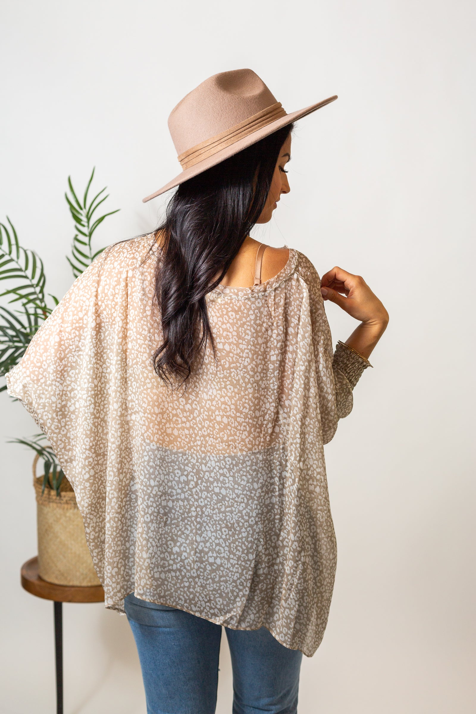 White leopard prints cover the fabric of this lightweight autumn top. Mid-length smocked cuff sleeves attach to a u-neckline on an oversized and sheer tunic bodice.