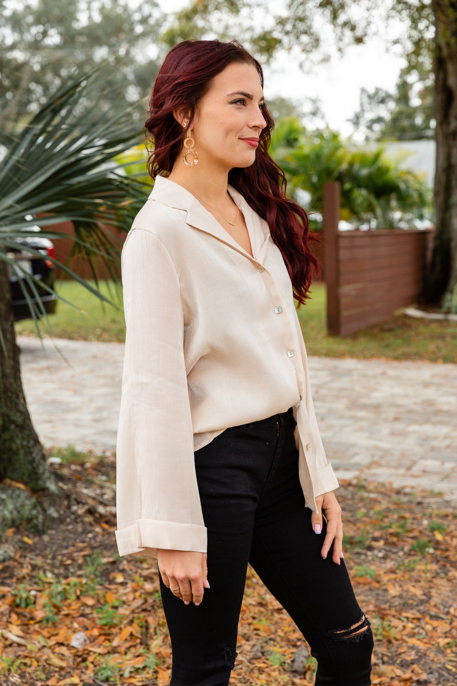 This champagne colored blouse has long banded button cuffed sleeves that attach to a collared button-down bodice that is oversized and relaxed.