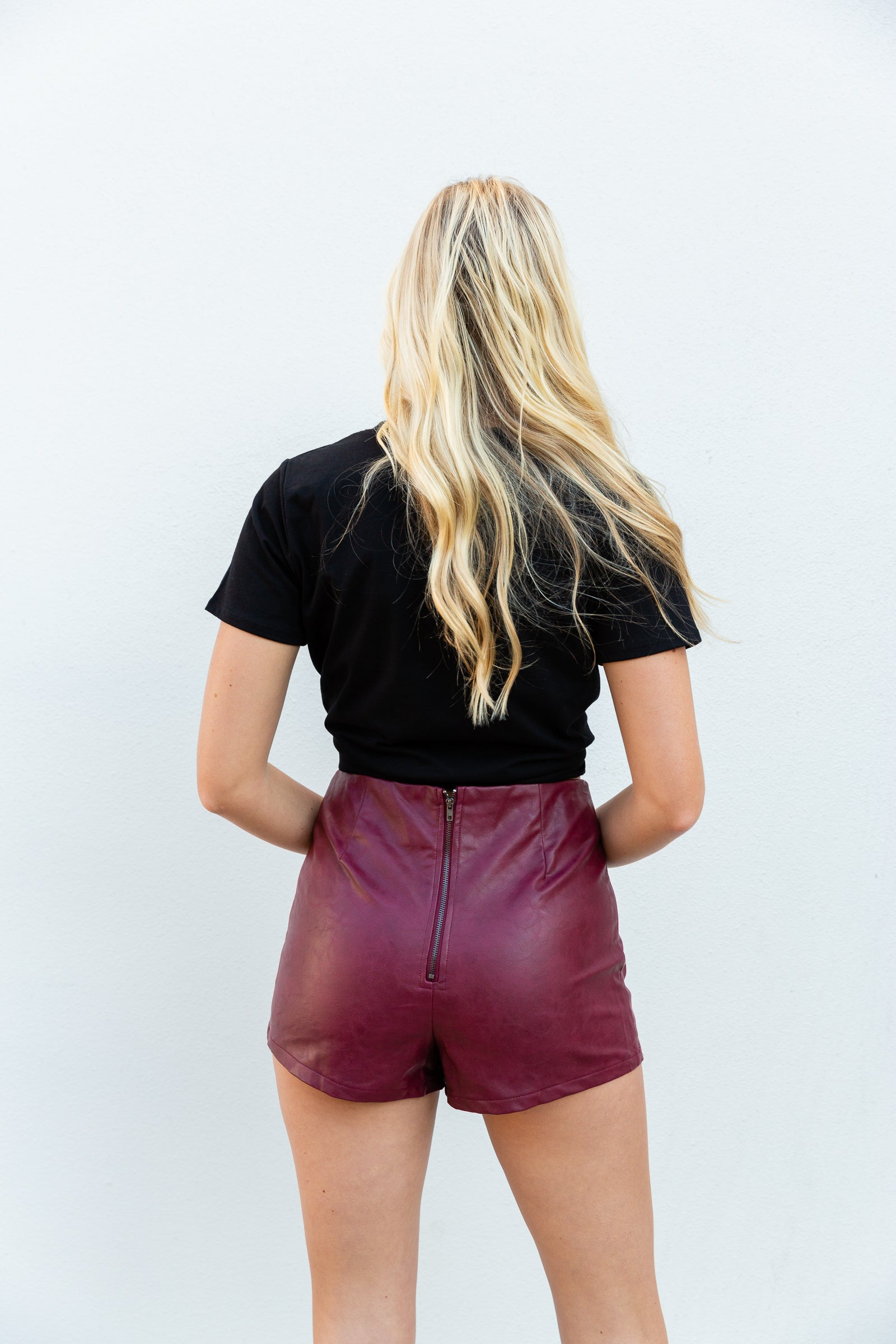 These bottoms could be paired with a variety of tops this season. This faux leather skort is fitted and has asymmetrical skirt panels that lay atop of fitted shorts.