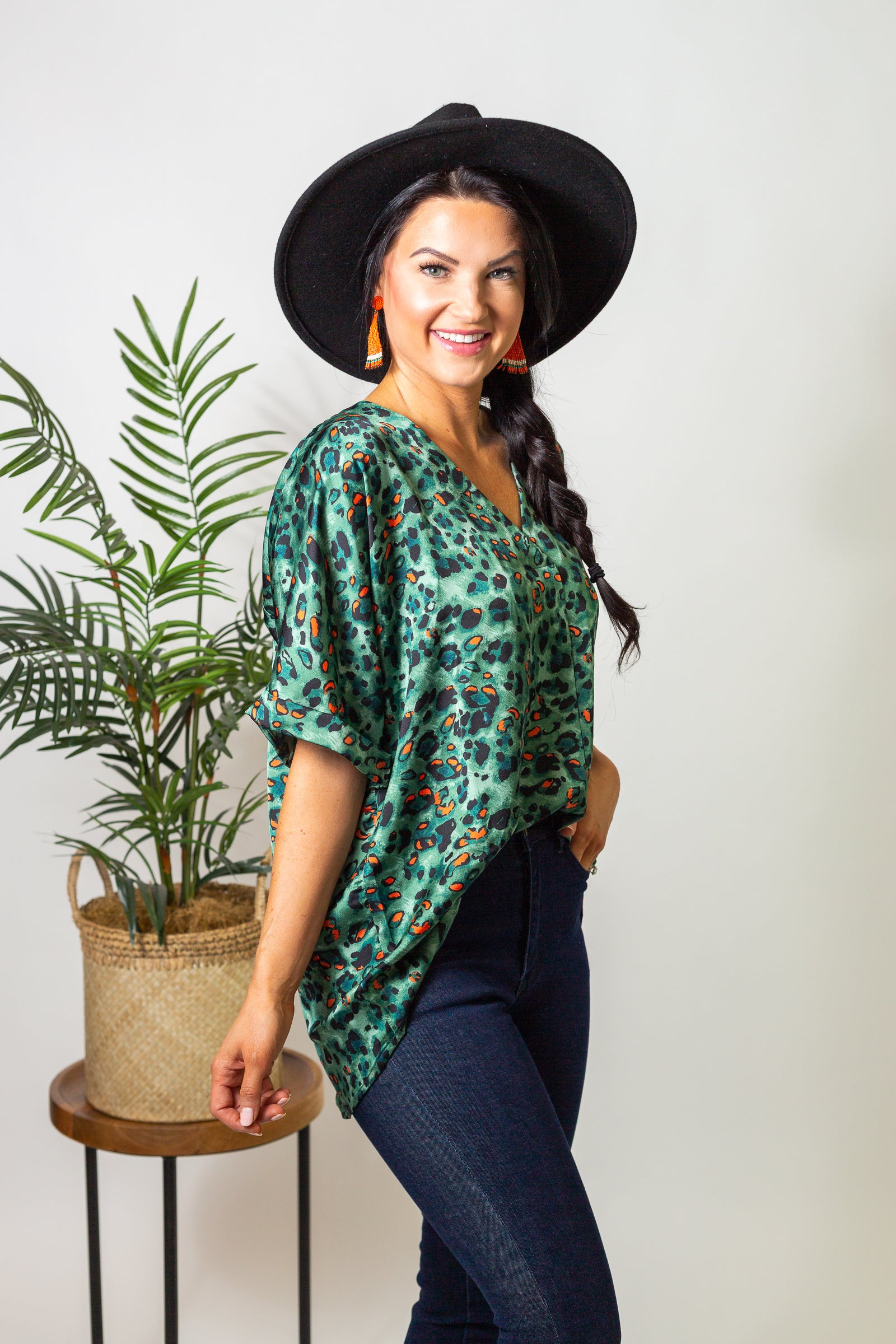 Leopard prints cover this satiny blouse, short cuffed sleeves that attach to a gentle surplice neckline with a folded over center detail on a loose and oversized bodice silhouette.