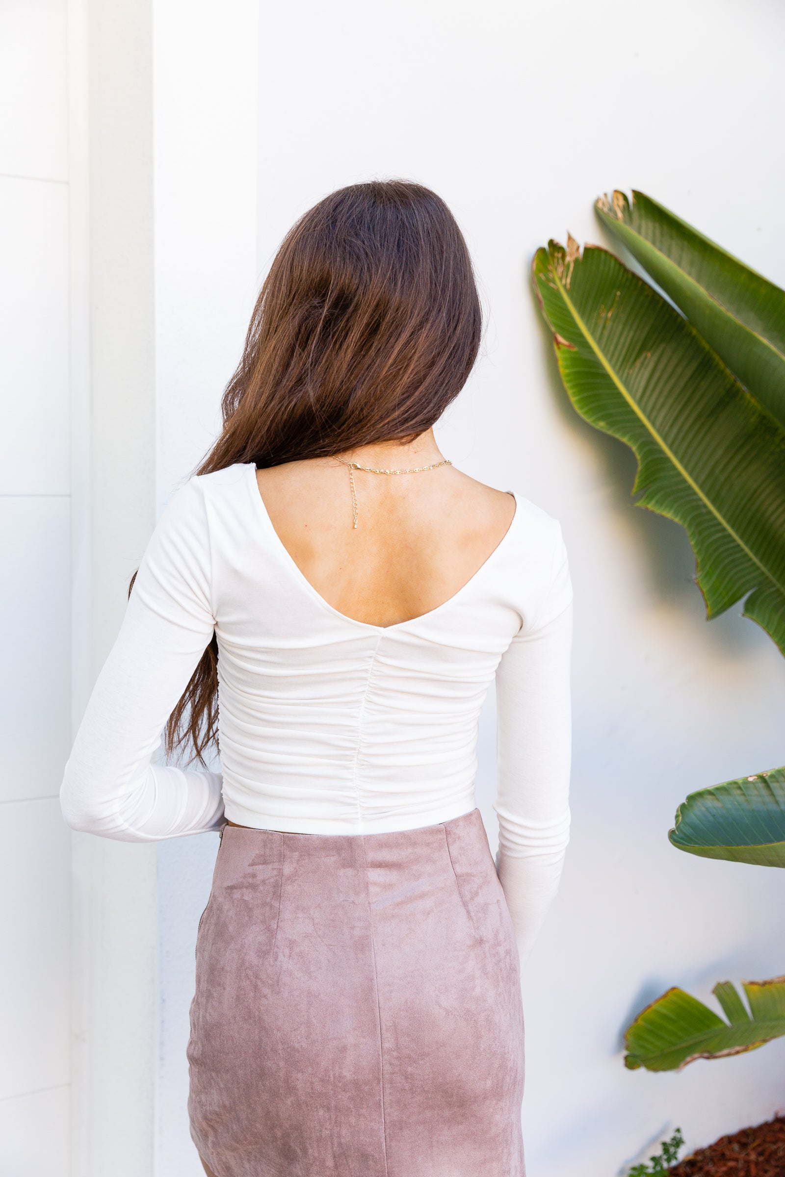 Long fitted sleeves attach to a v-neckline on a ruched-center and fitted bodice silhouette with a cropped hem. Style this white ruched top with a variety of bottoms.