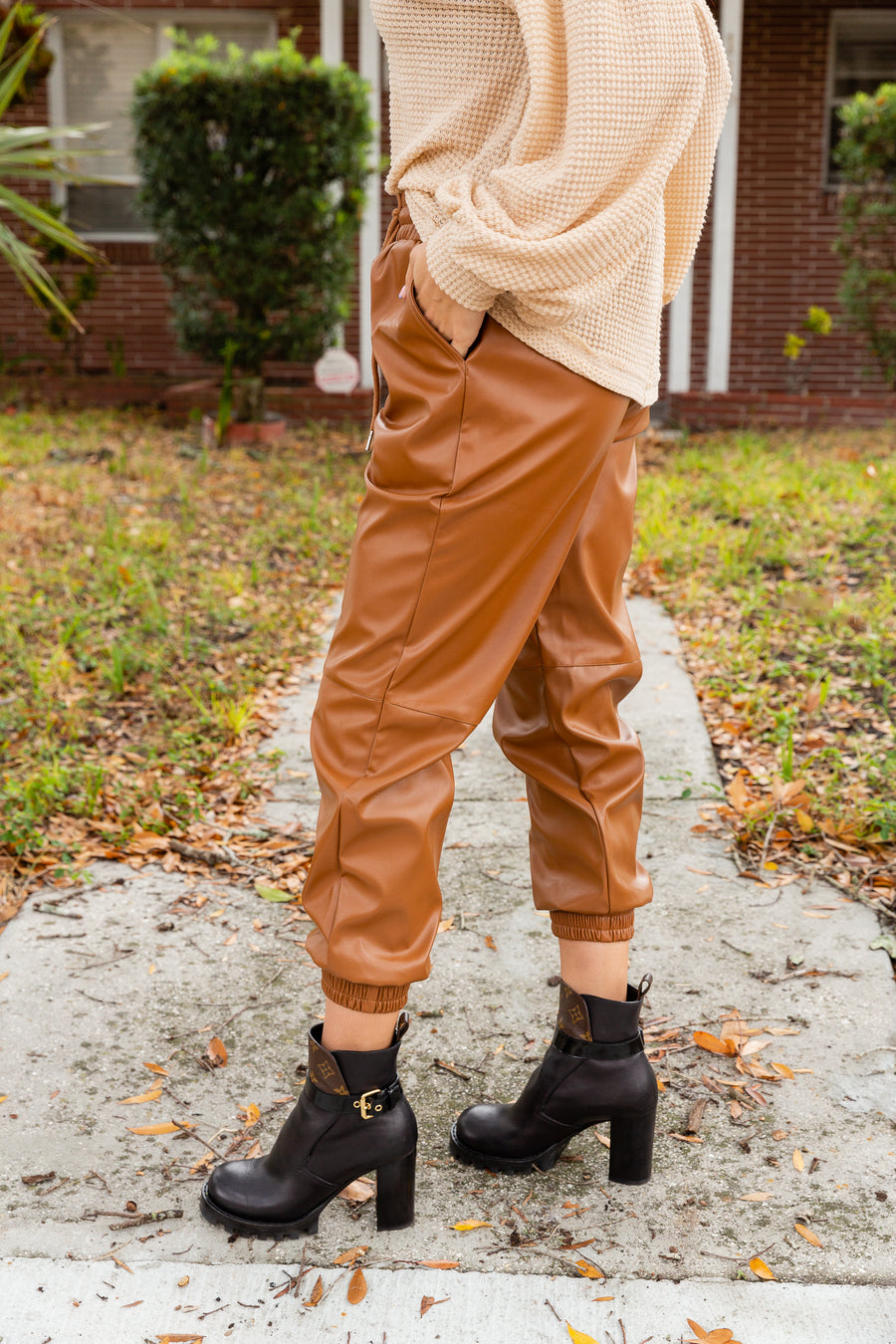 These pleather joggers have an elastic waistband with a drawstring tie before leading into relaxed-fit pants with side pockets and tapering into skinny pant legs with an elastic ankle cuff.