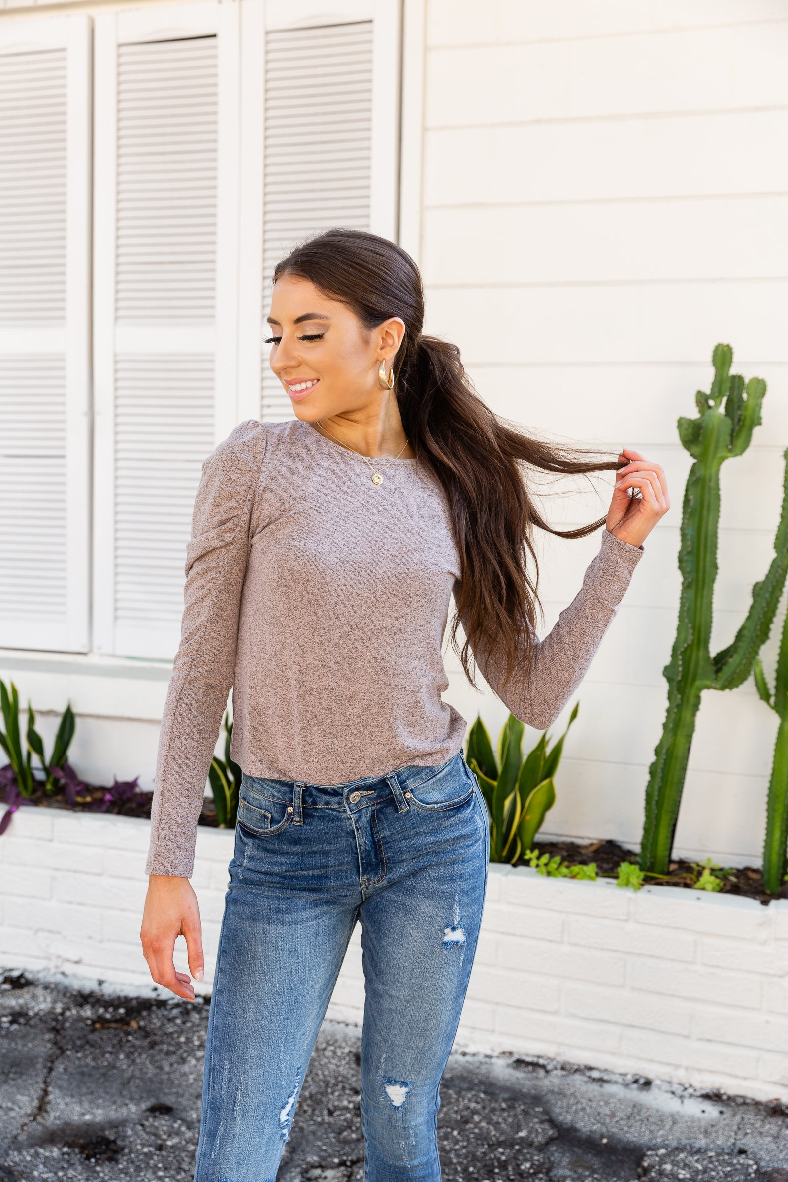 Long sleeves with puffed shoulders attach to a rounded neckline on a comfortably fitted bodice silhouette. Style this easy autumn top with jeans.
