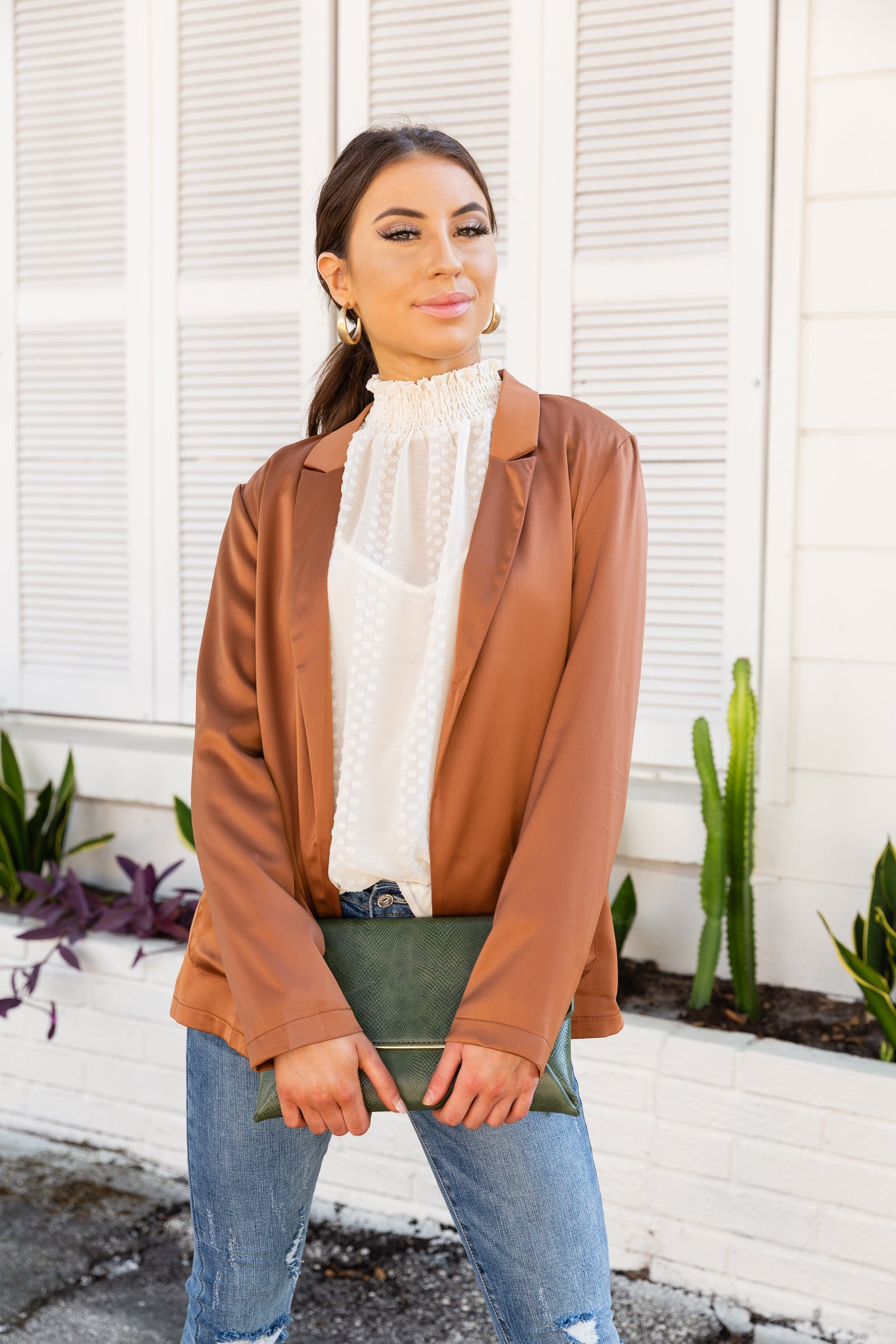 This lightweight and satiny blazer has long sleeves that attach to a collared neckline on an open-front and oversized bodice with front pockets,