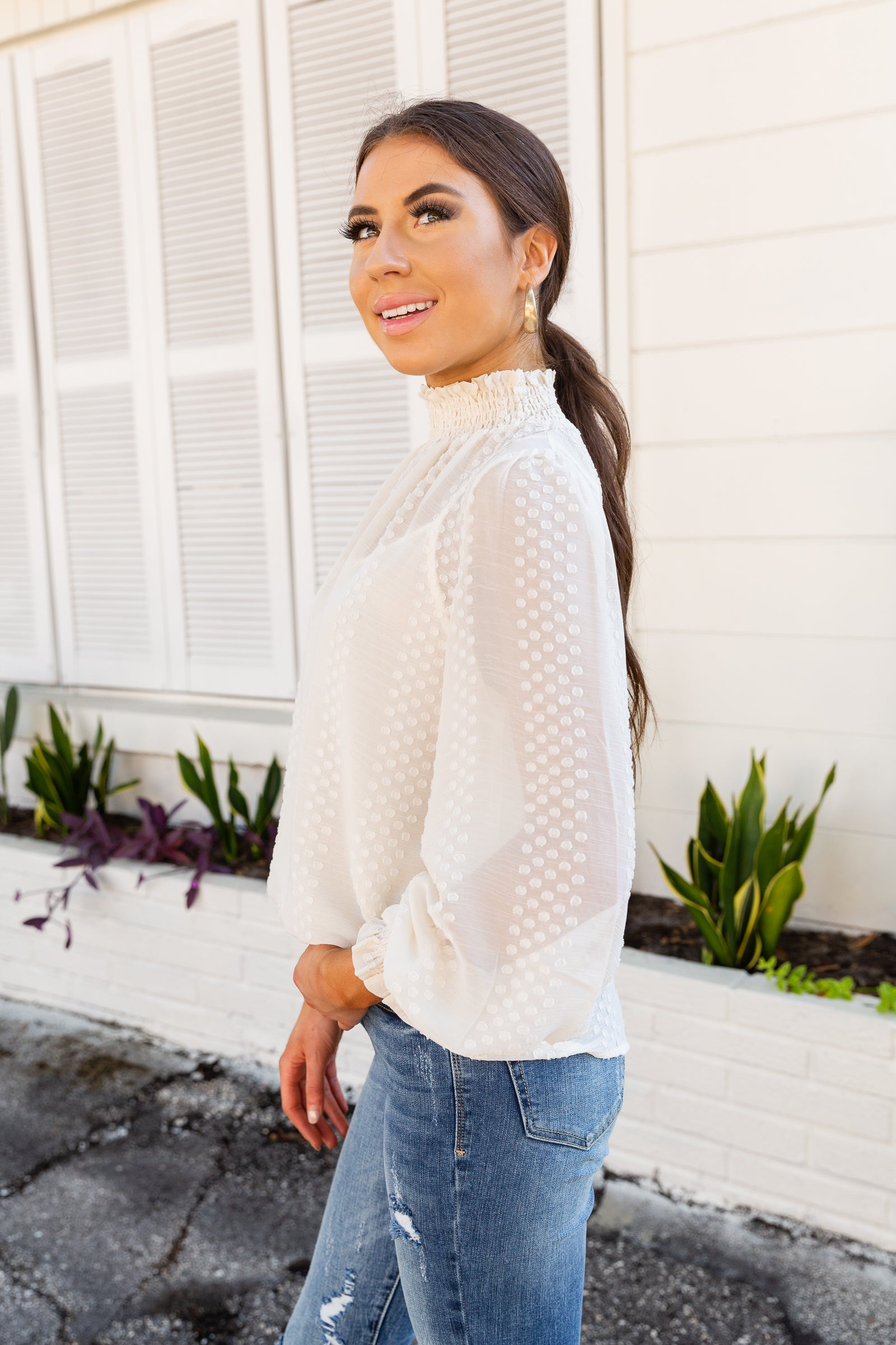 Long elastic ruffled sleeve top has swiss dots that cover the lightweight fabric. High smock banded neckline that leads to a comfortable and relaxed bodice silhouette.