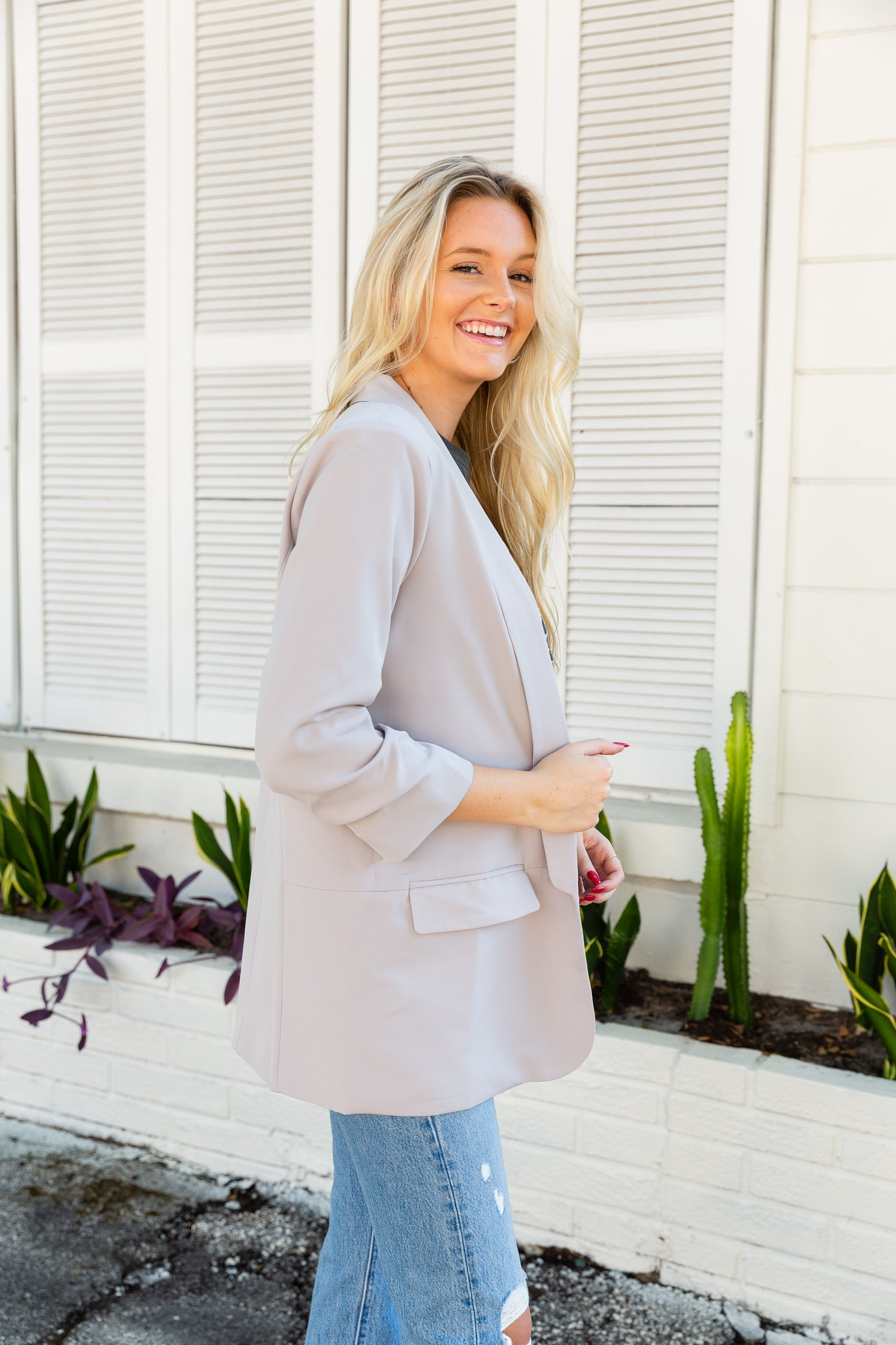Mid-length ruched detail sleeves attach to a collared neckline on an oversized-fit open front bodice that has faux pocket flaps on the side of the blazer and a fully lined interior.