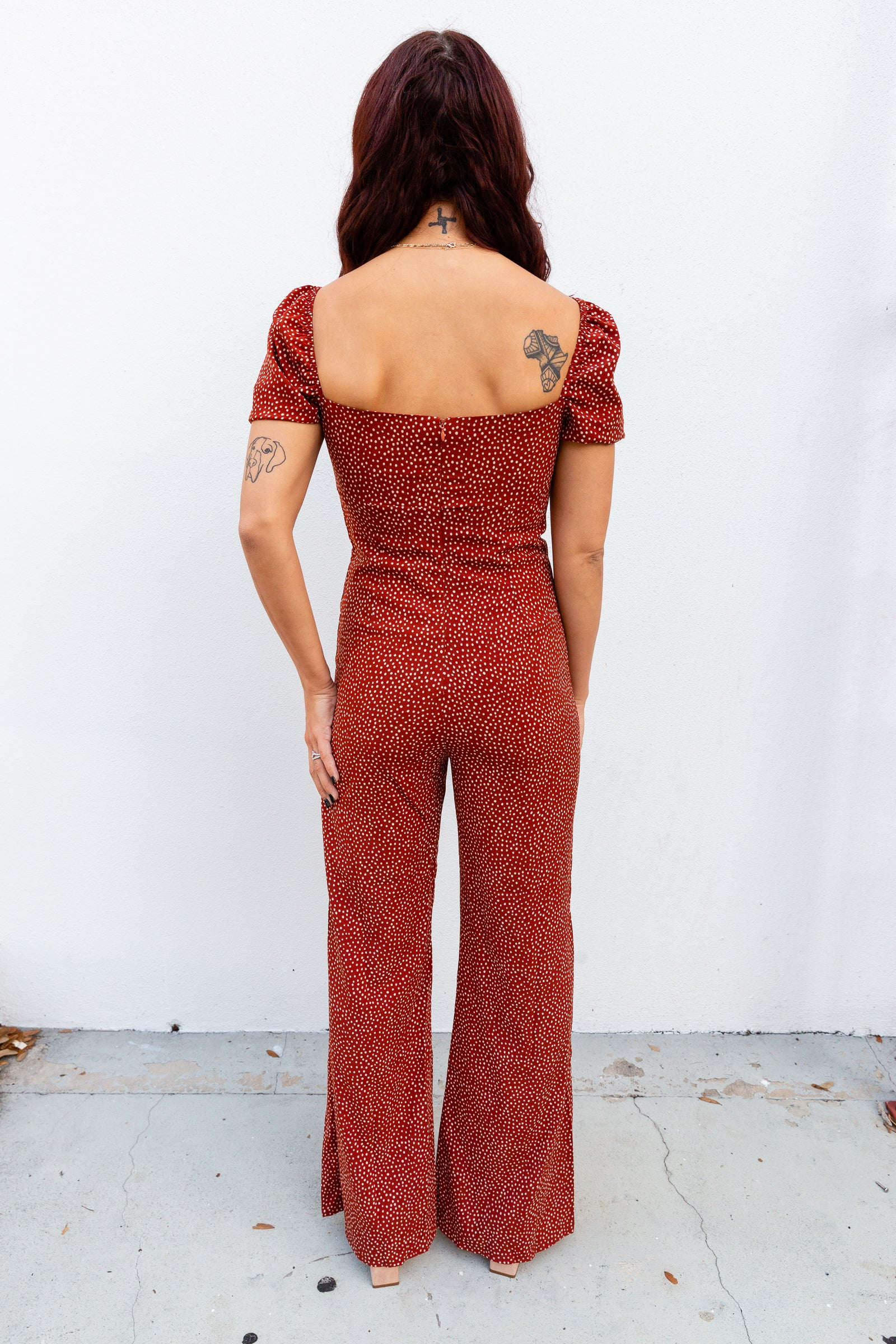 This polka dot printed jumpsuit has short elastic cuffed sleeves that attach to a v-neckline on a fitted bodice with a tie front hem and leads down into flowy and gently flared pant legs.