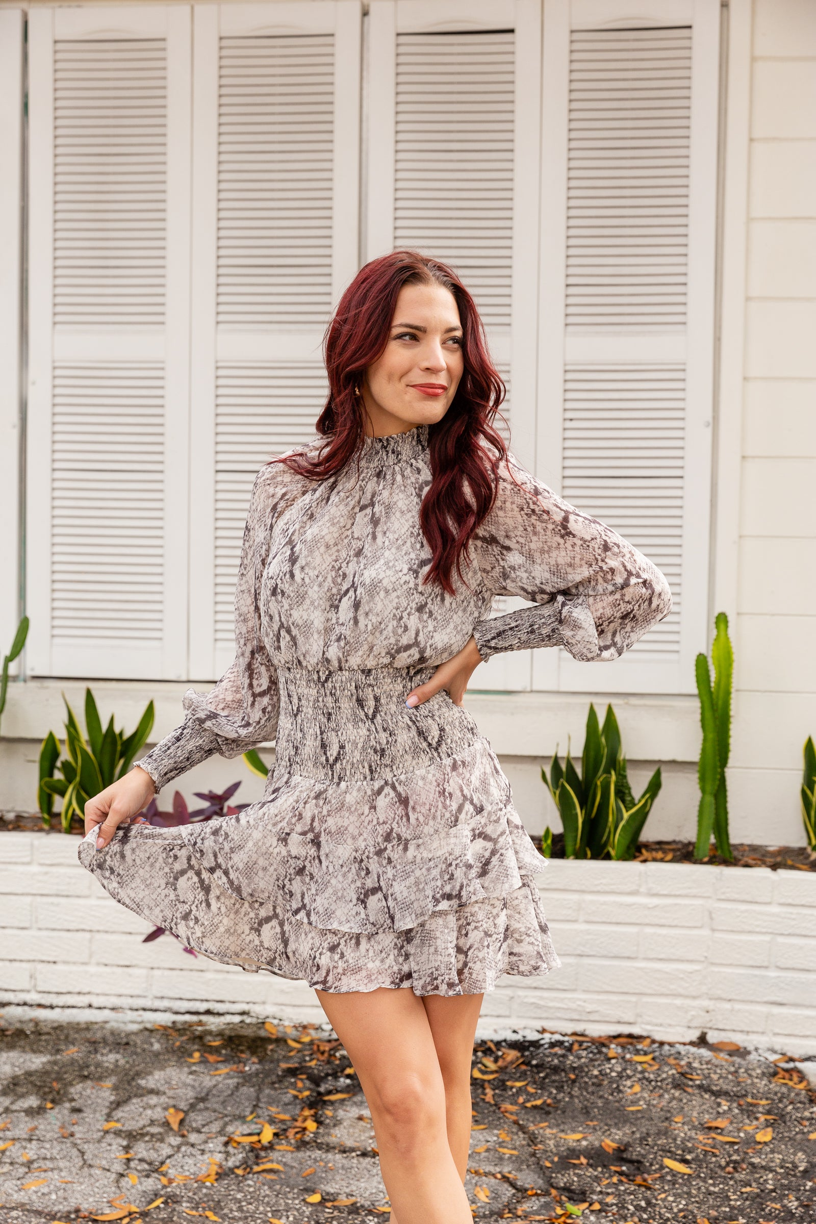 Long smock cuffed sleeves attach to a smocked mock neckline on a relaxed fit bodice before meeting a smocked waistband and flowing down into a ruffle layered mini skirt.
