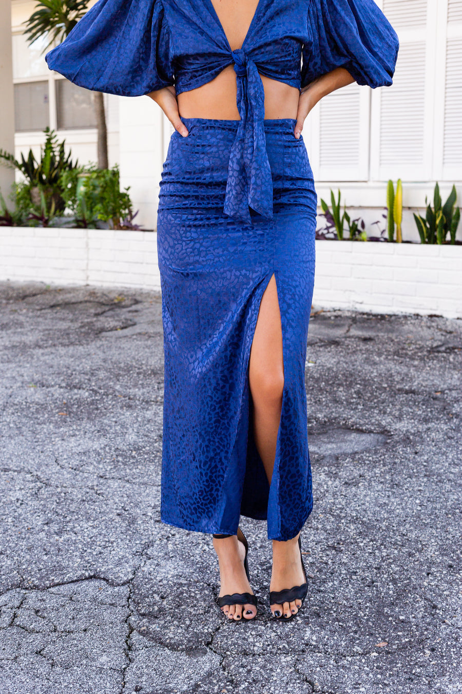 This skirt has a fitted waistband that leads down a darted and parallel cut skirt with a slit at the front. It meets in the middle of the calves for a classic midi skirt look.