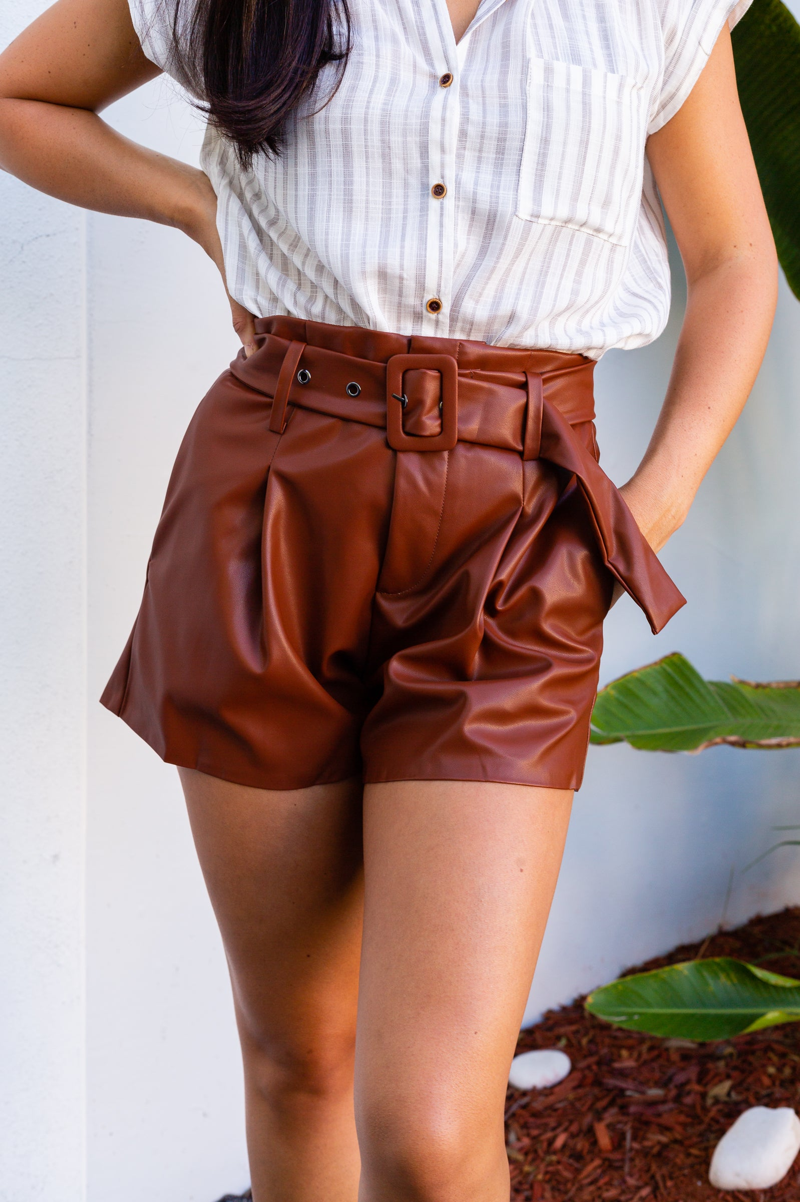 These pleather shorts have a fitted waistband with belt loops secured with a clasp and button front with a zipper fly and go down into a pleated and relaxed fit shorts.