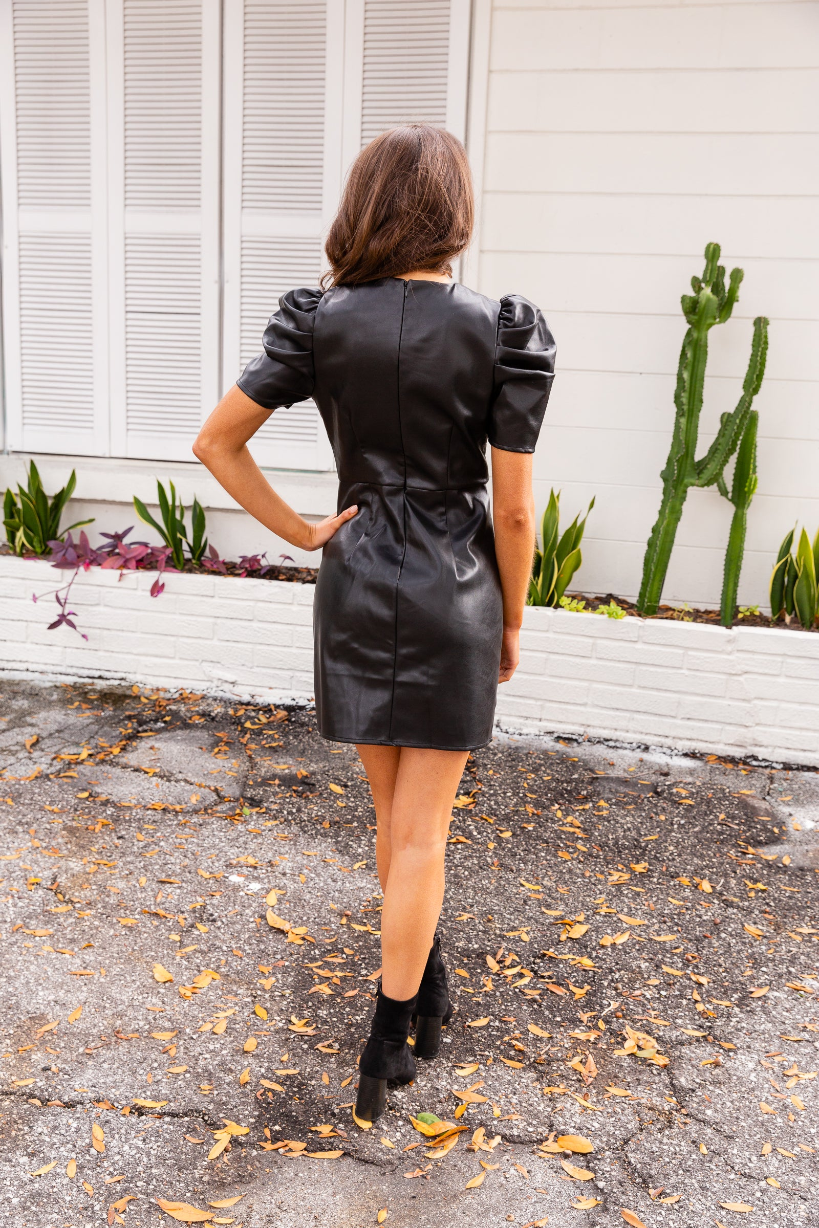 Short puffed shoulder sleeves attach to a high u-neckline on a fitted and darted bodice before meeting a fitted waistband and going into a straight mini skirt.
