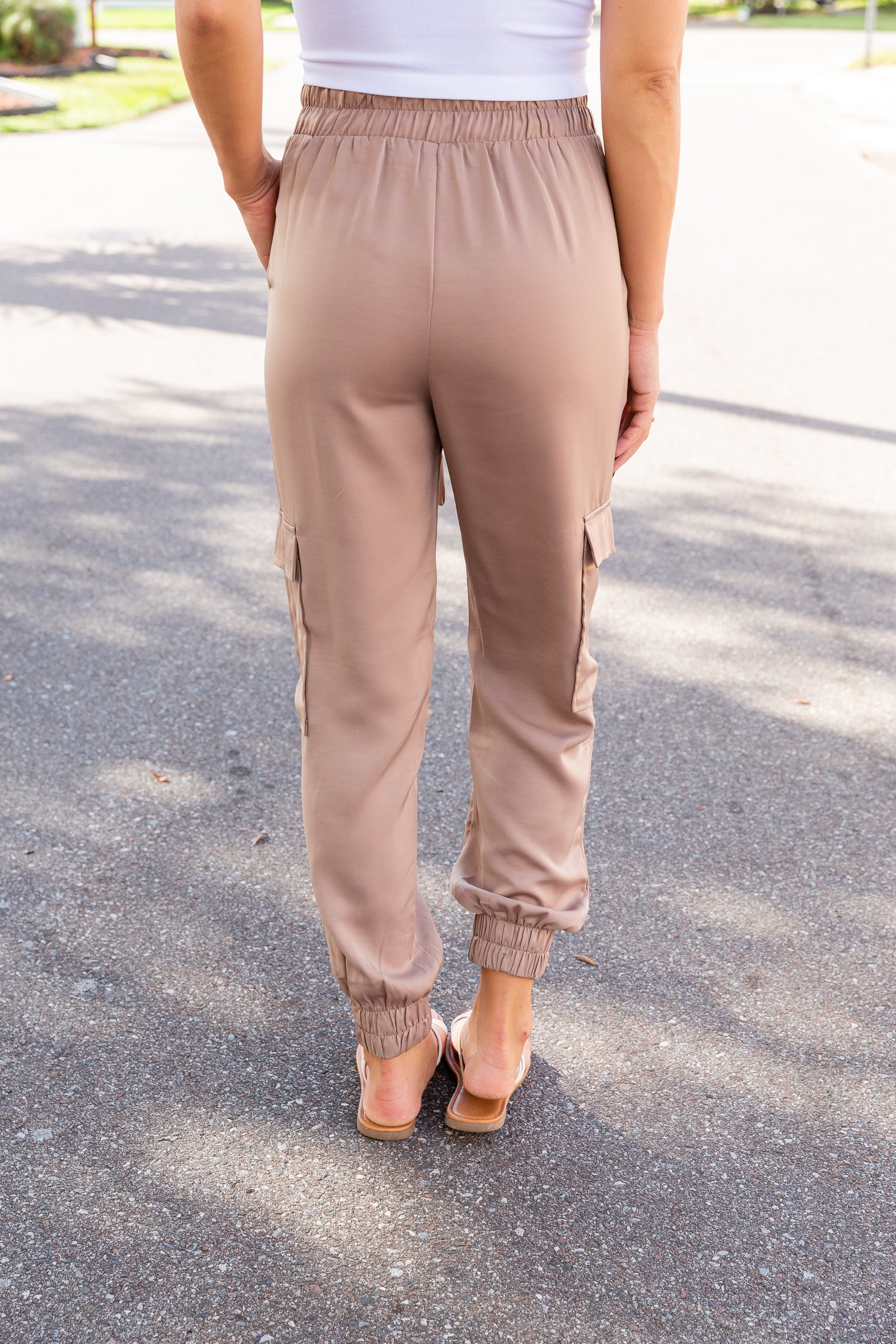 Adjustable drawstring waist leading to pockets at the side and go down into relaxed pant legs, accommodating one pocket at the side of the thigh, and meets strap details at the ankles.