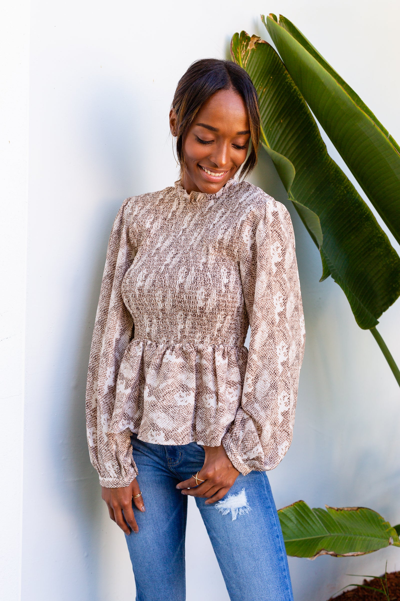 This brown snake printed top has long button banded sleeves that attach to a high ruffle neckline on a smocked bodice and leads to a ruffle hem that flares out.
