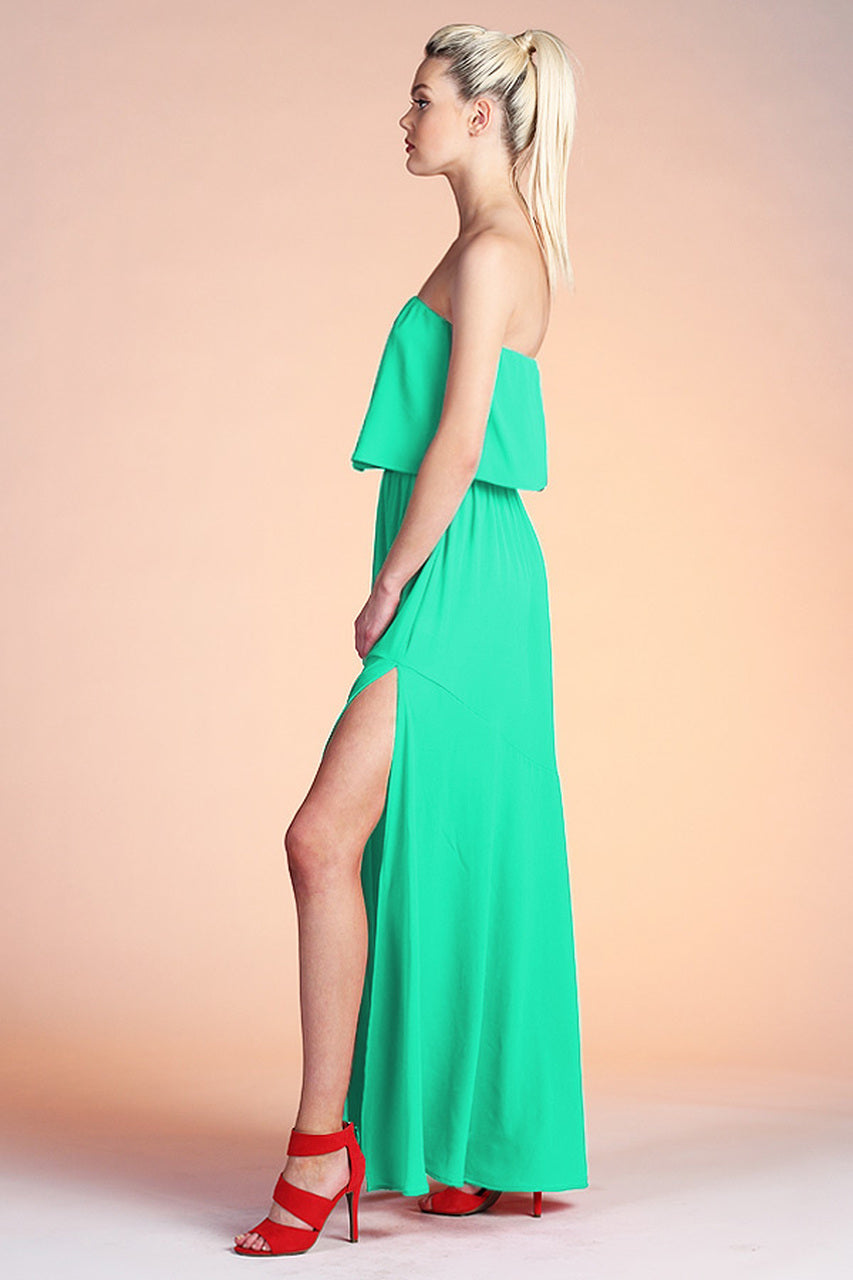 Strapless neckline on a flounce bodice silhouette and meets an elastic waistband. It flows down into a long maxi skirt with asymmetrical panel detail and a side slit at the side.