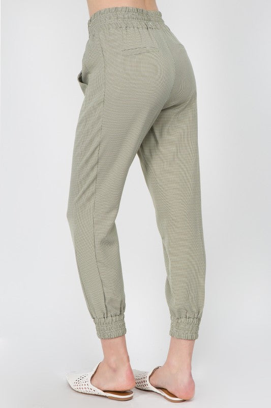 These gingham printed joggers have an elastic waistline highlighted with a faux tie, side pockets, faux back-pockets, and elastic ankle cuffs.