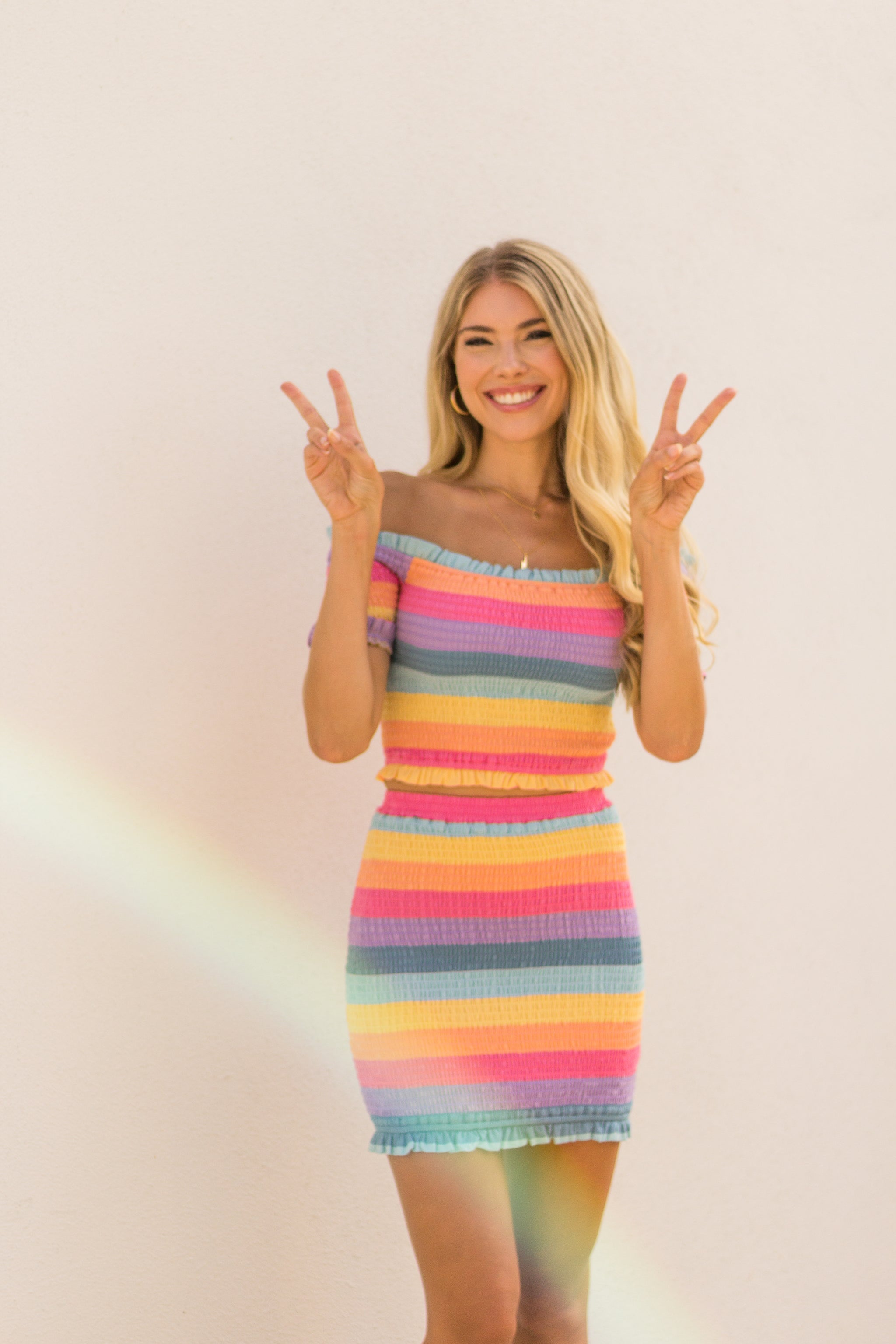 Bright and bold rainbow colors stripe this stretchy and smocked skirt. This printed skirt has a ruffle hem at the bottom and hugs your body to accentuate your curves.