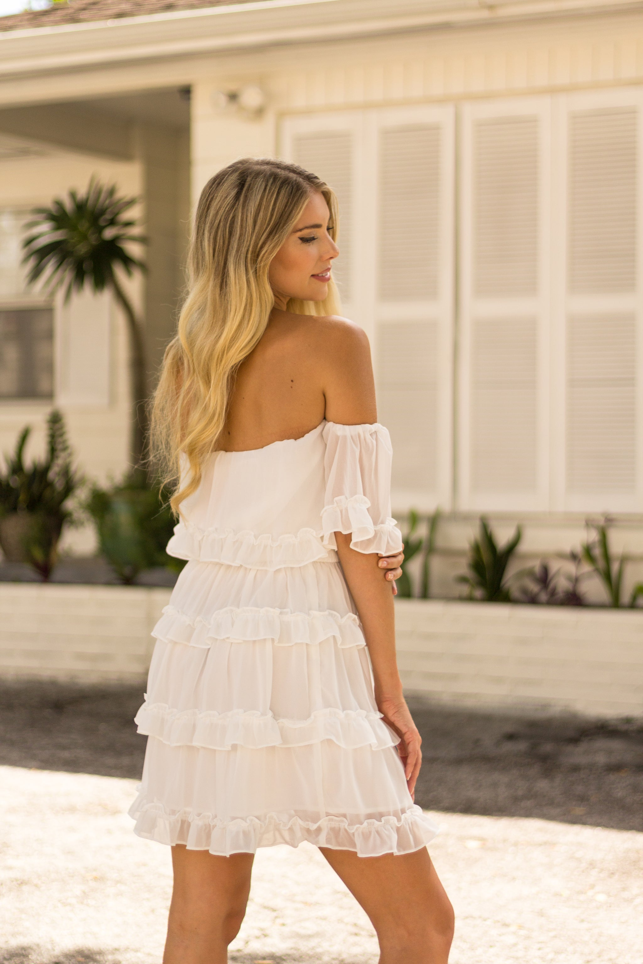 Short off-the-shoulder sleeves that attach onto a straight neckline on a relaxed flounce bodice with a ruffle trim meeting a smocked waistband down into a ruffled short a-line skirt.