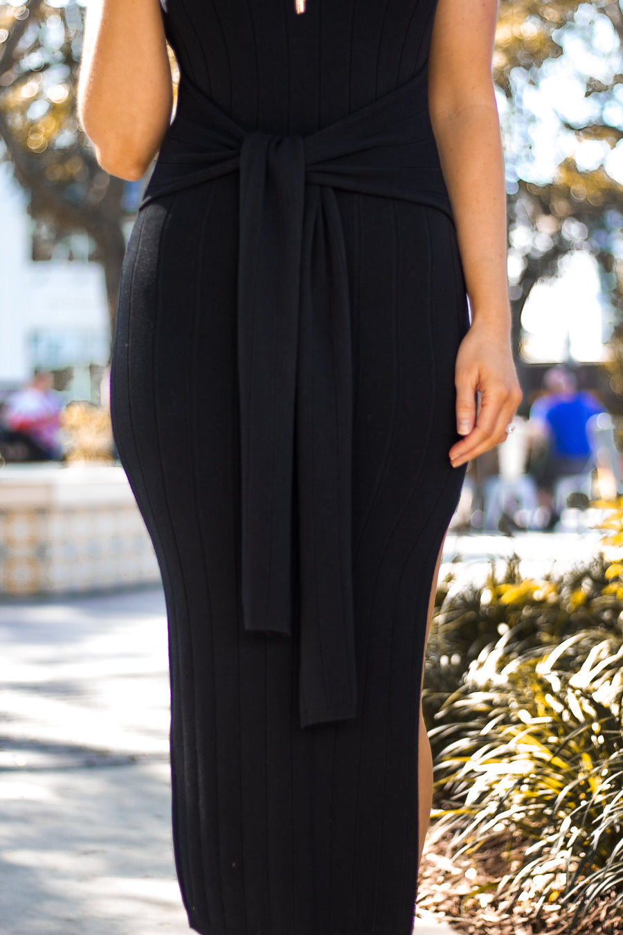 Thick straps attach to a u-neckline and lead to a knit fitted bodice and skirt silhouette with fabric ties that come out from the sides and could be tied in the front.