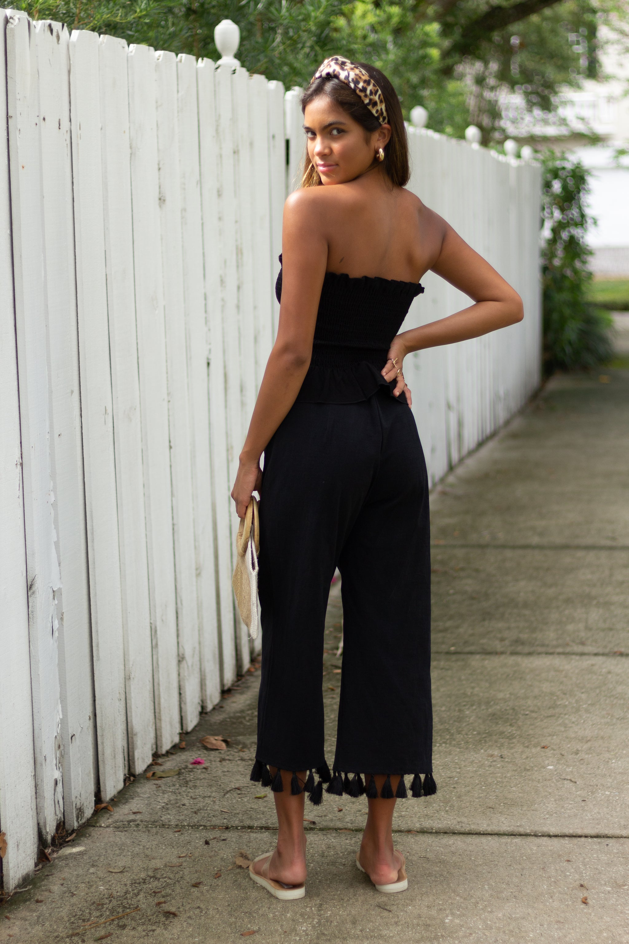These black pants have a fitted waistband and go down to relaxed wide pant legs and end in a high-water style with tassels across the bottom hem.