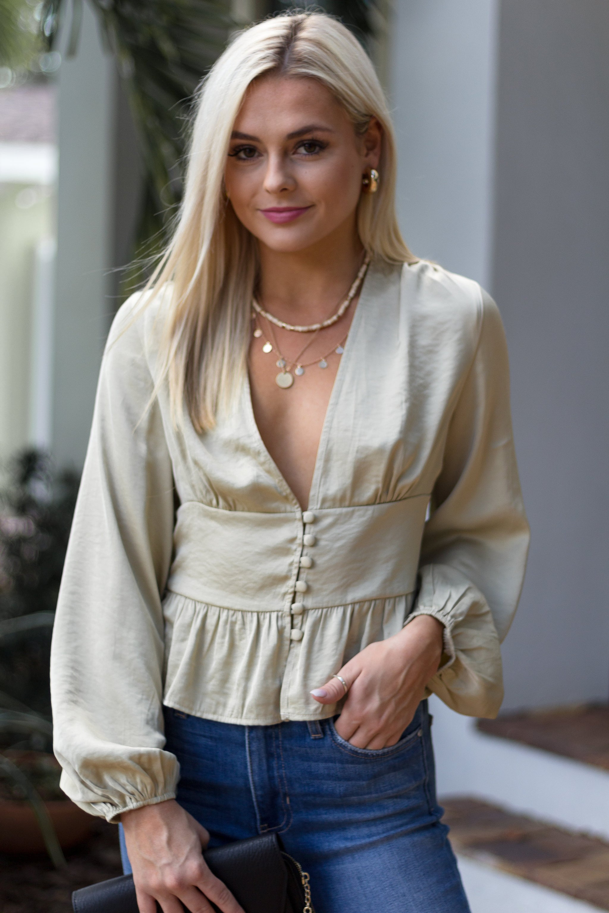 Long puffed elastic cuffed sleeves attach to a deep v-neckline and lead down to a banded waistband with buttons down the bodice and flares into a peplum style hem.