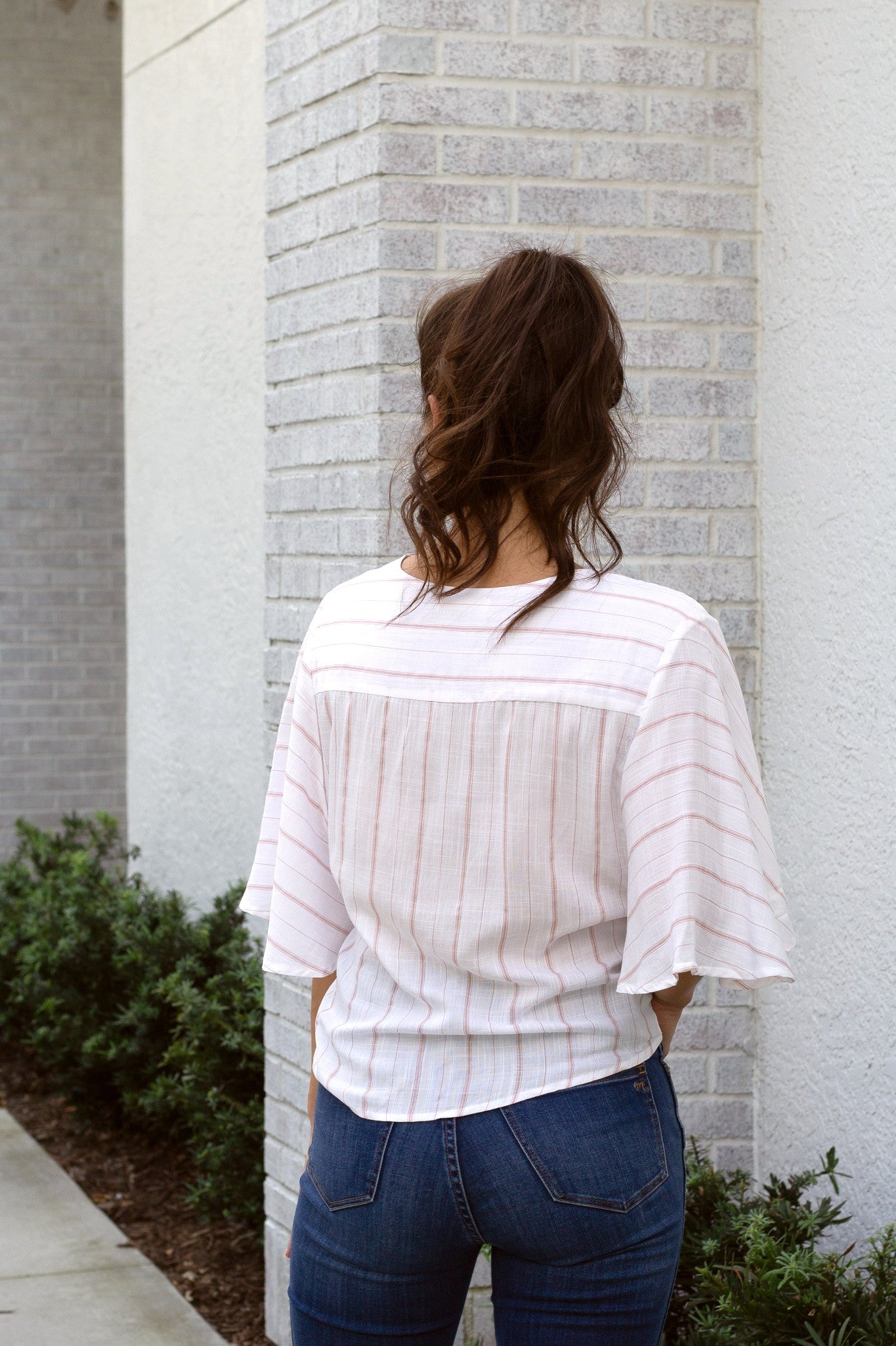 Pink pinstripes on a white background create this airy blouse with short, flowy sleeves on a surplice neckline, relaxed bodice and looping hem