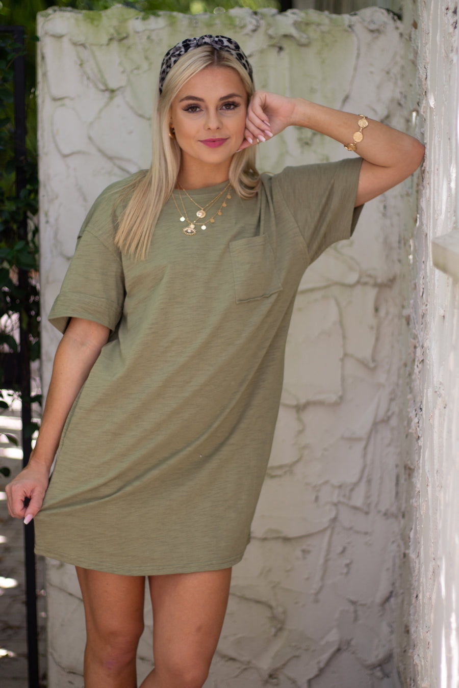 This heathered and lightweight dress has short sleeves that attach to a high rounded neckline into a t-shirt style silhouette with a front pocket at the chest and pockets.