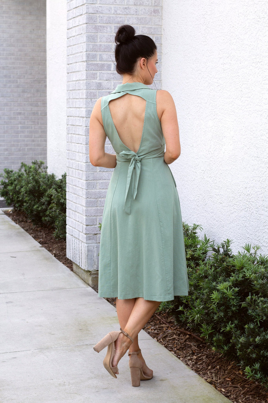 Sage midi dress has a sleeveless, notched collar neckline with an empire bodice, button-down silhouette with a fit and flare skirt accented with a tie feature.