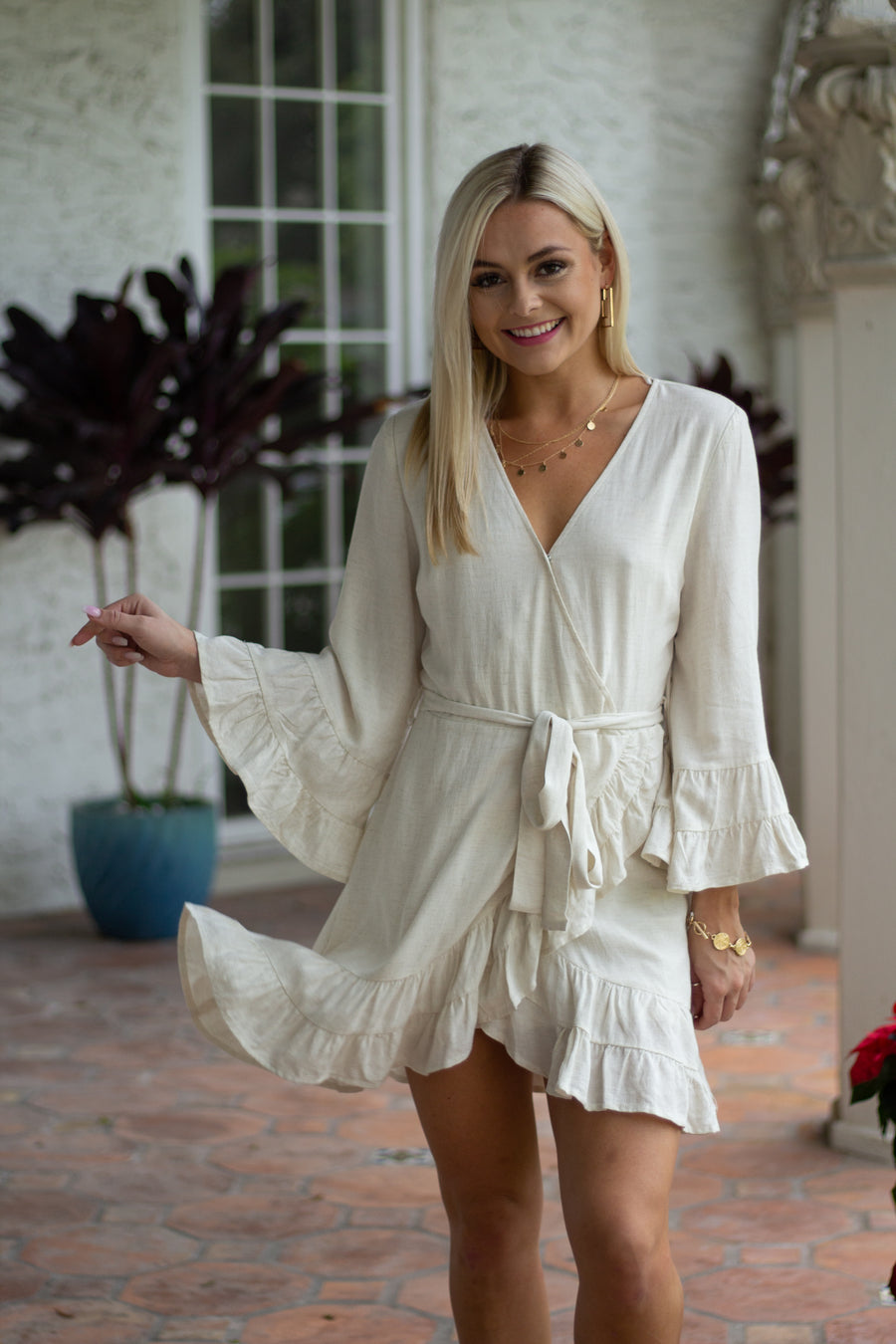 This lightweight dress has long tiered ruffle cuffed sleeves that attach to a surplice neckline and fitted and darted bodice. It flows into an asymmetrical ruffle mini skirt.