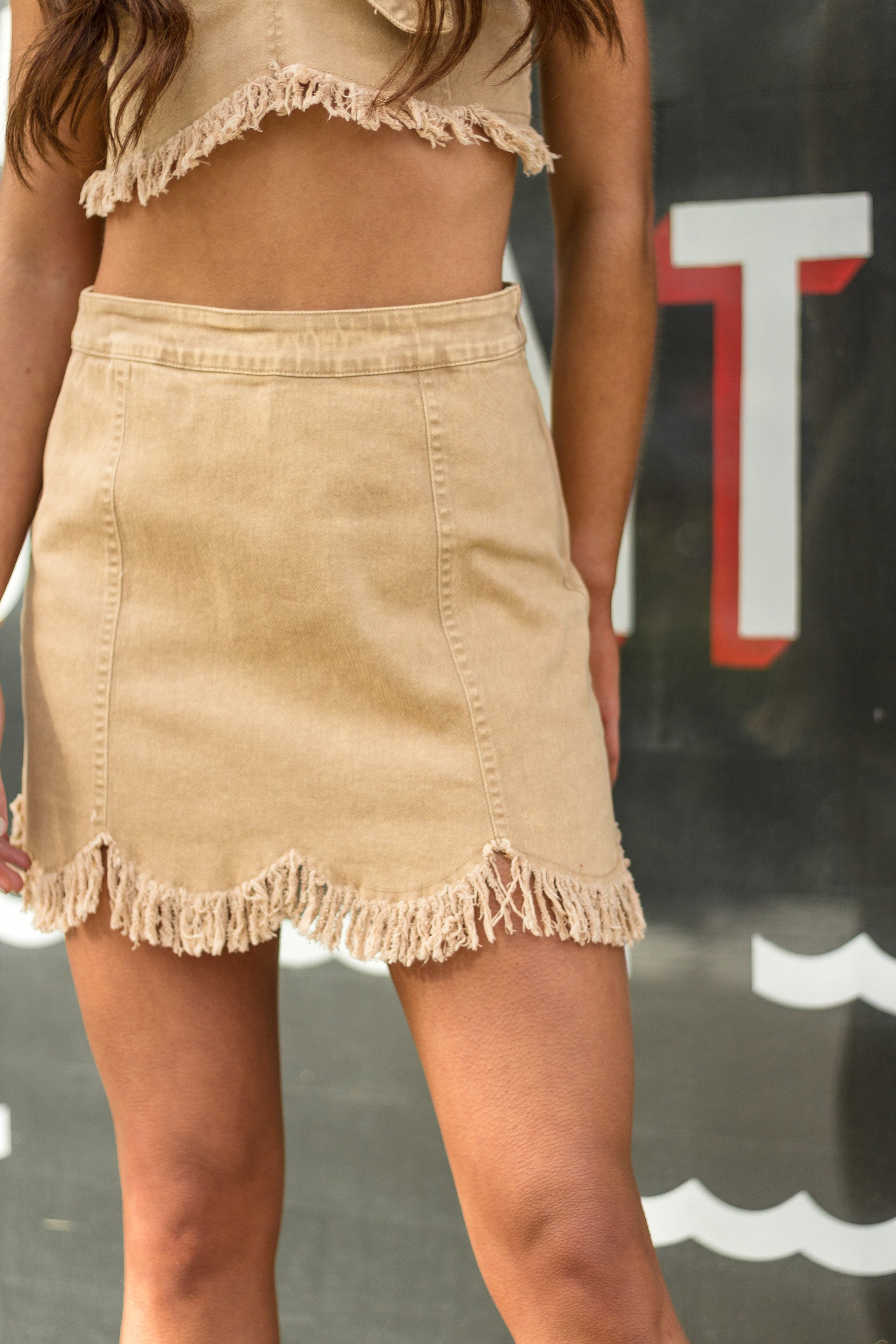 This trendy skirt has a fitted waistband that leads down a paneled and hip-hugging mini skirt with a scalloped hem with small tassel fringes dangling at the bottom hem.