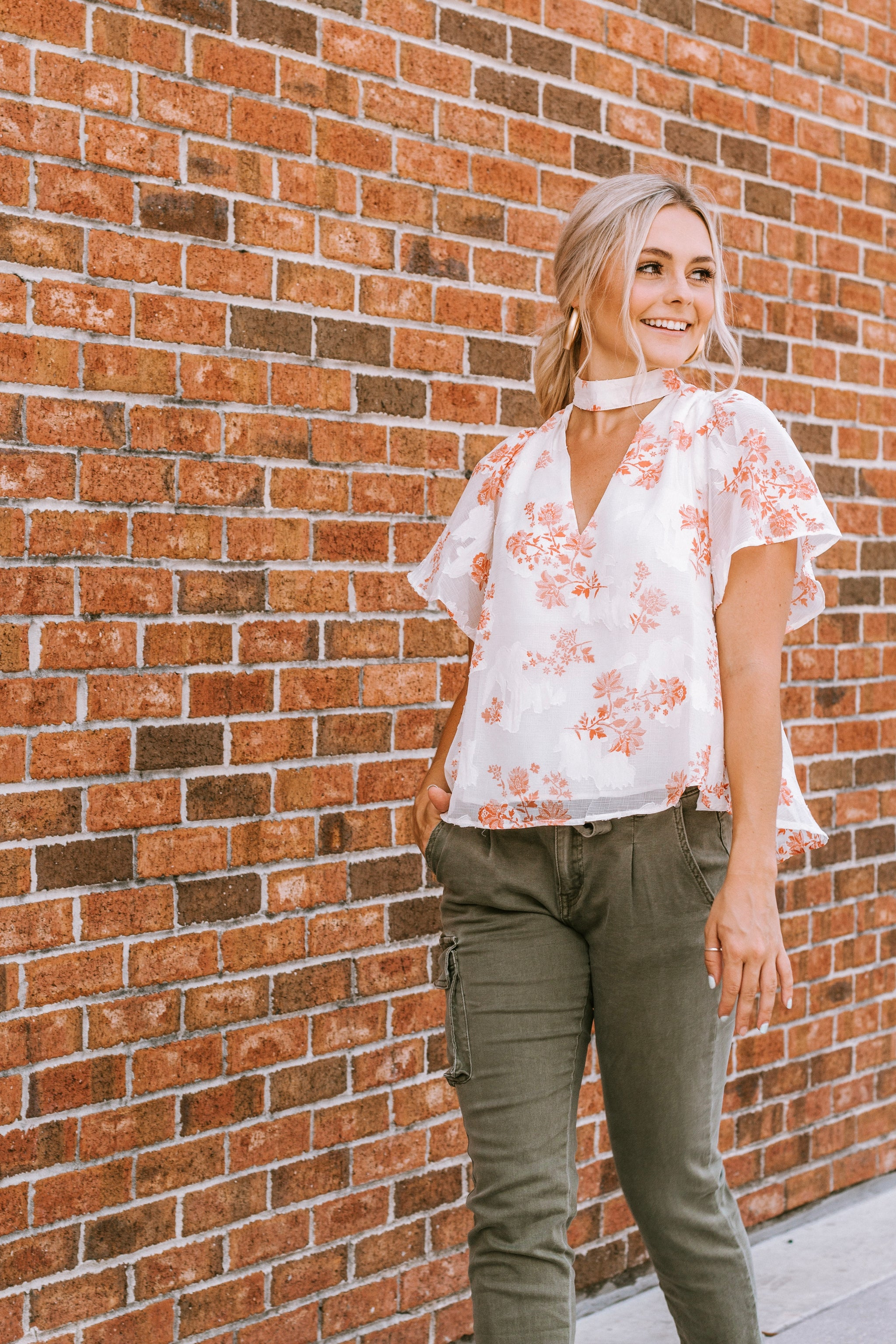 This lightweight top features a high, mock neckline with a v-cut out, relaxed bodice and flowy silhouette with short flutter sleeves.