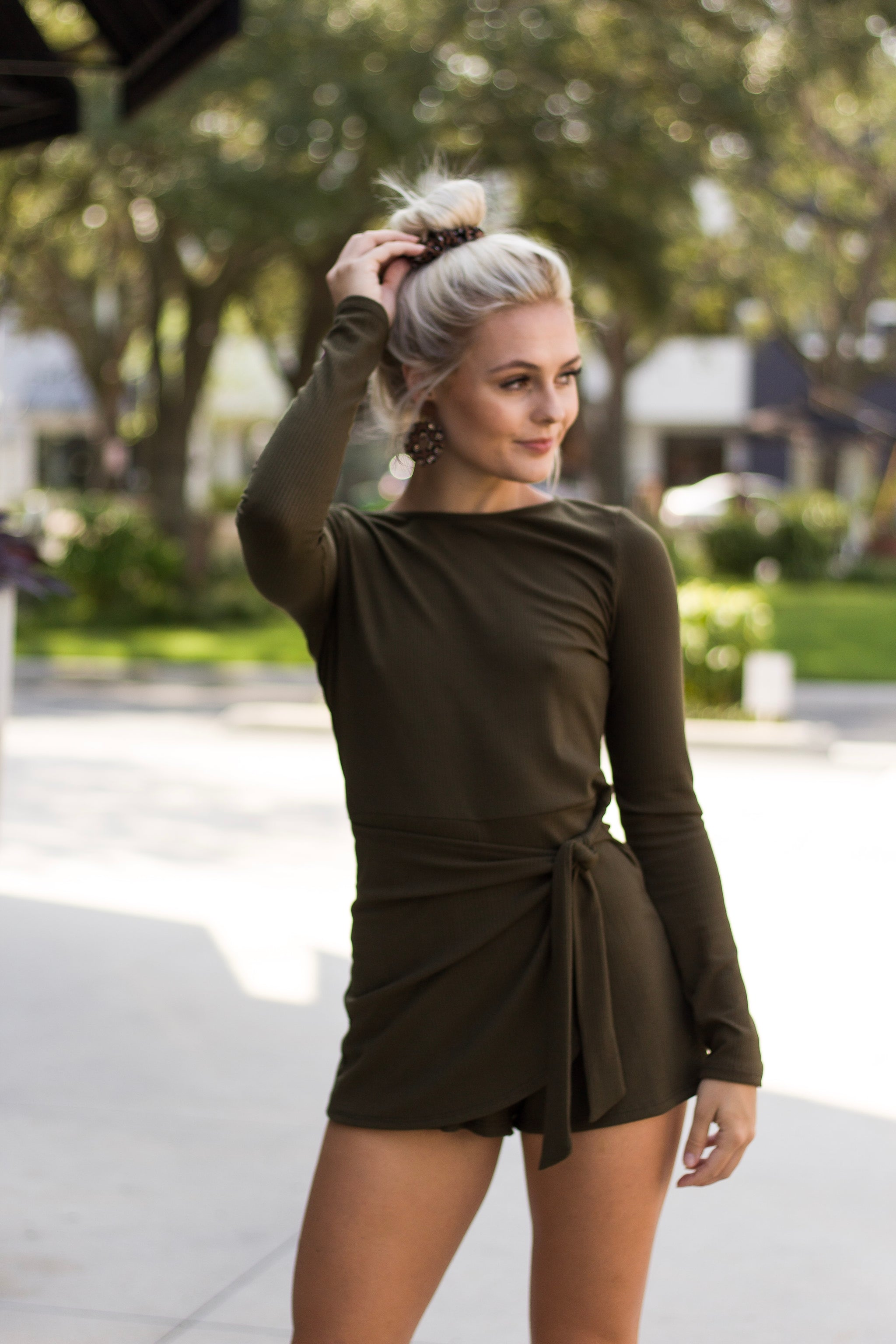 This long-sleeved ribbed romper has a u-neckline and a fitted knit bodice that leads to fitted shorts that has a skirt flap panel that ties at the side.