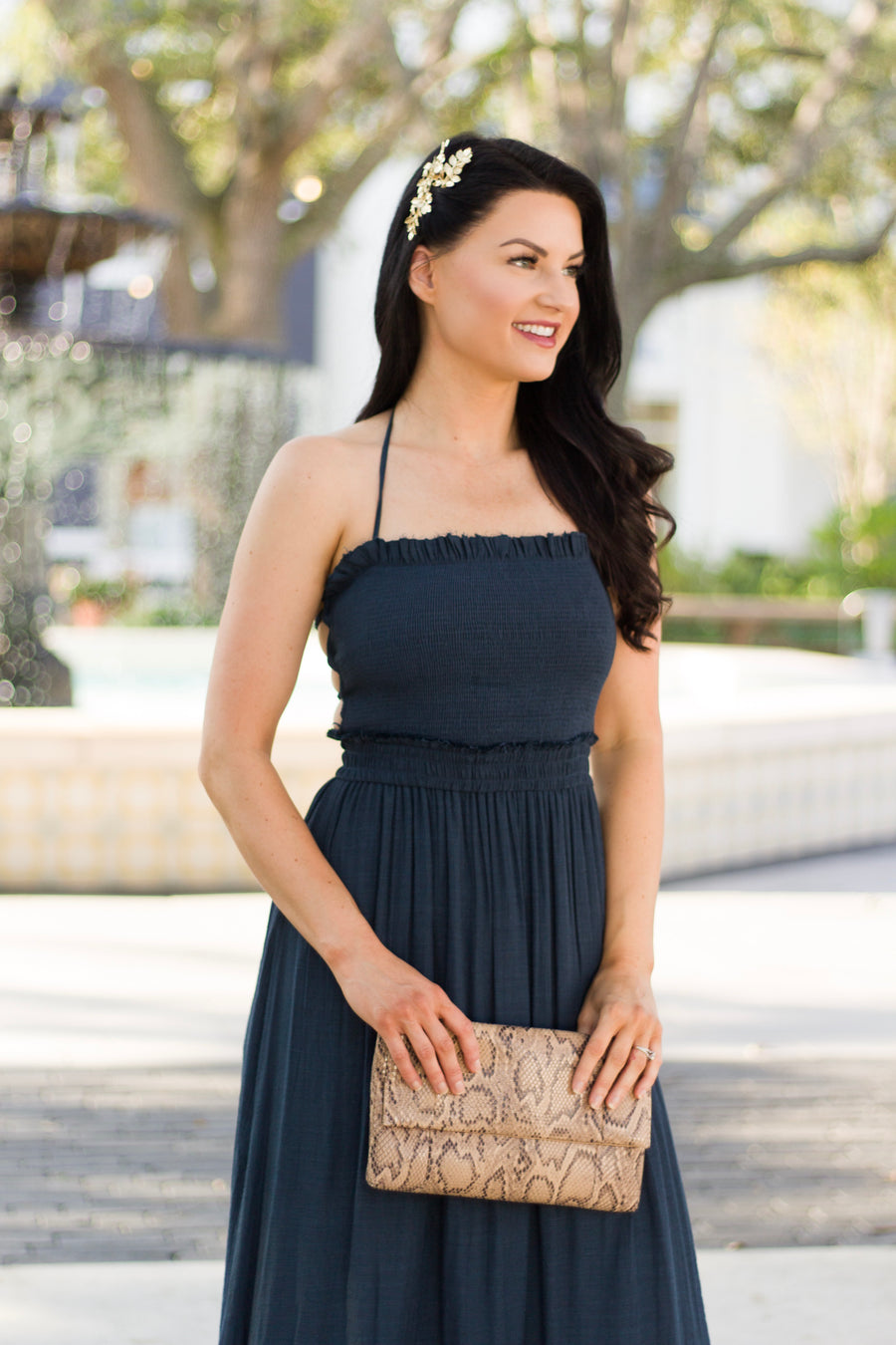 Thin halter straps that attach to a straight neckline smocked bodice and lead to an elastic waist that flows into a layered and tiered ruffle skirt.