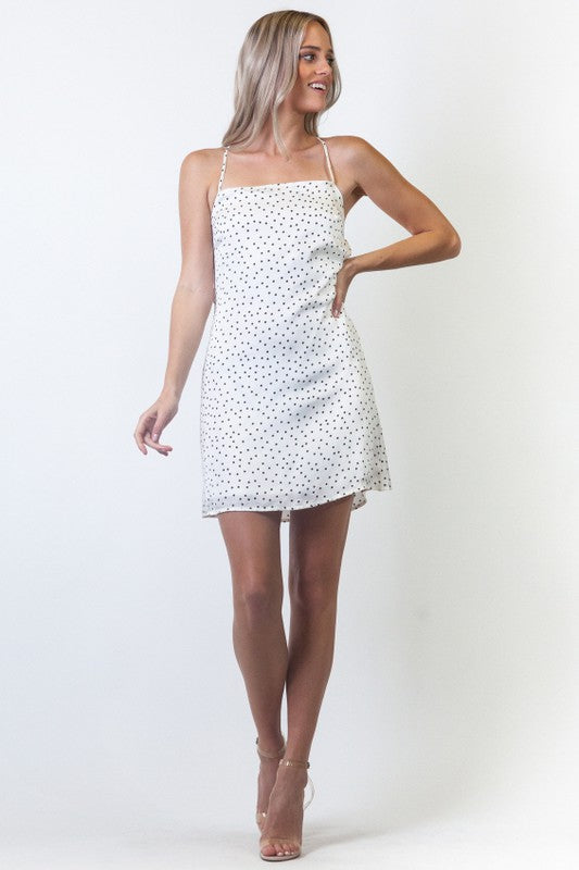 Dotted dress as thin straps that attach to a straight neckline with a criss-cross back and tied back that leads down to a simple bodice with flattering a-line skirt silhouette.