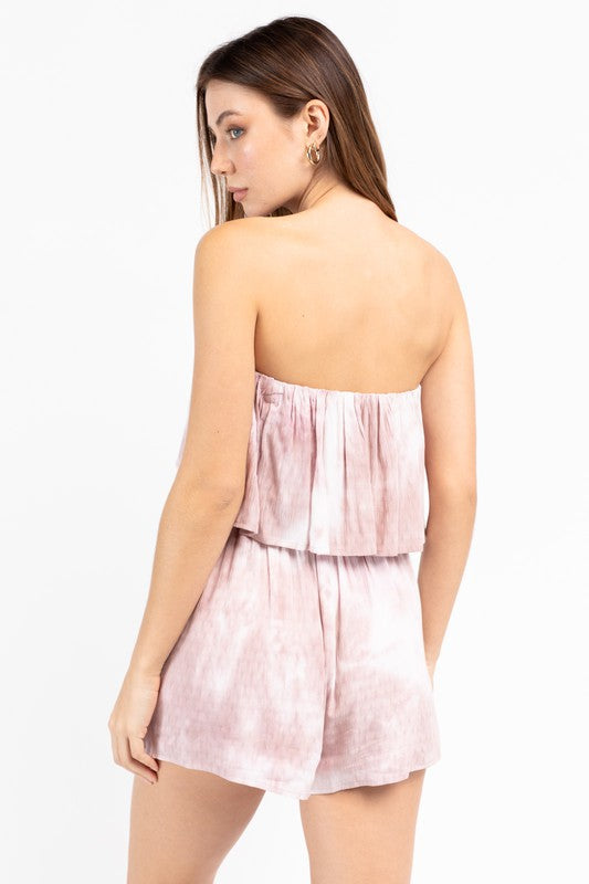 This lightweight and tie-dye printed romper has a straight neckline on a flounce bodice before meeting an elastic waistband and flowing down into relaxed shorts.