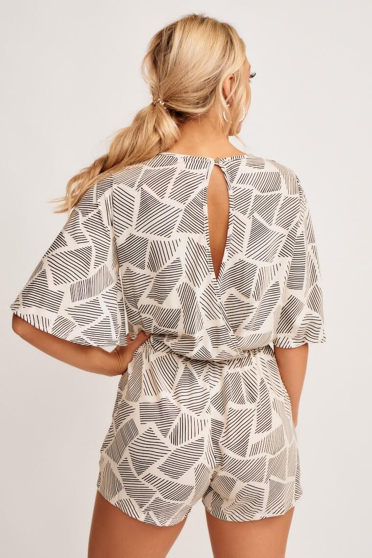 Blackline prints detail this lightweight, short sleeve romper has a v-neckline, flowy bodice with a tie front hem and an elastic waist that goes into relaxed shorts.