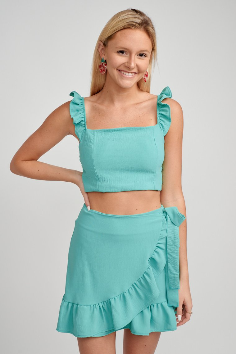 Ruffled straps attach to a straight neckline on a fitted and princess darted cropped bodice. This crop top features a zipper on the back.